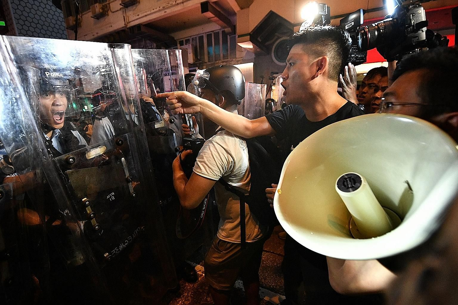 """Hong Kong Legislative Council members Au Nok-hin ( with loud hailer) and Jeremy Tam clashing with police in Mongkok on Sunday. The protesters are now planning to """"stress test"""" targets like the Bank of China and broadcaster TVB in their bid to pressur"""