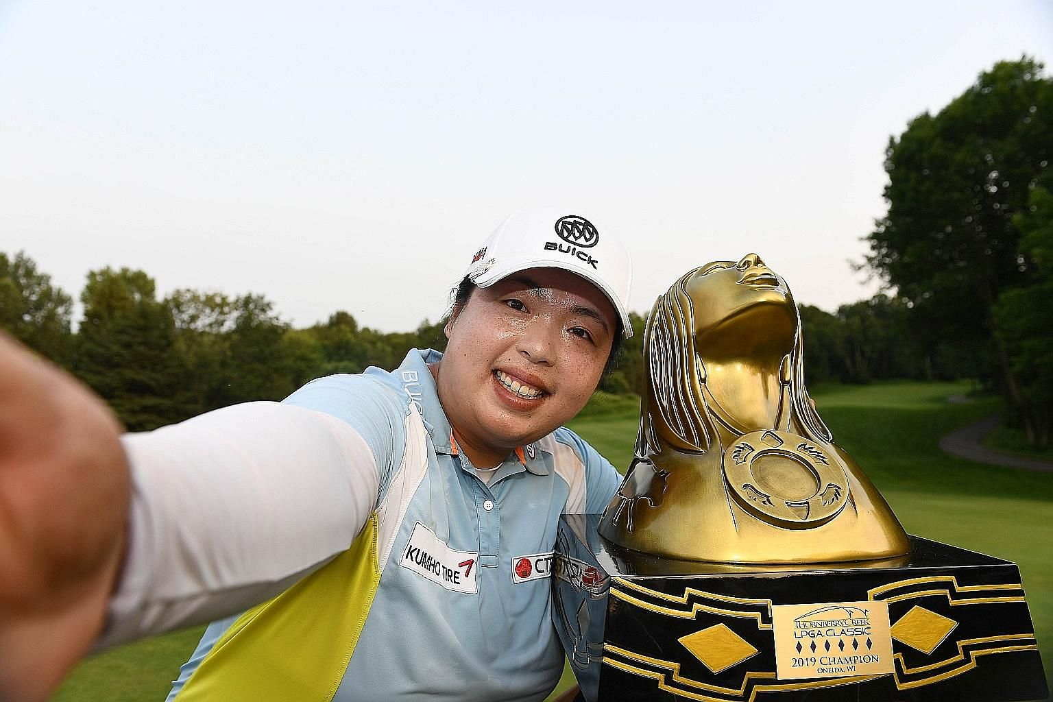 "China's Feng Shanshan imitates taking a ""selfie"" as she poses with the Thornberry Creek Classic trophy. She beat Thai Ariya Jutanugarn by one shot on Sunday in Oneida, Wisconsin."