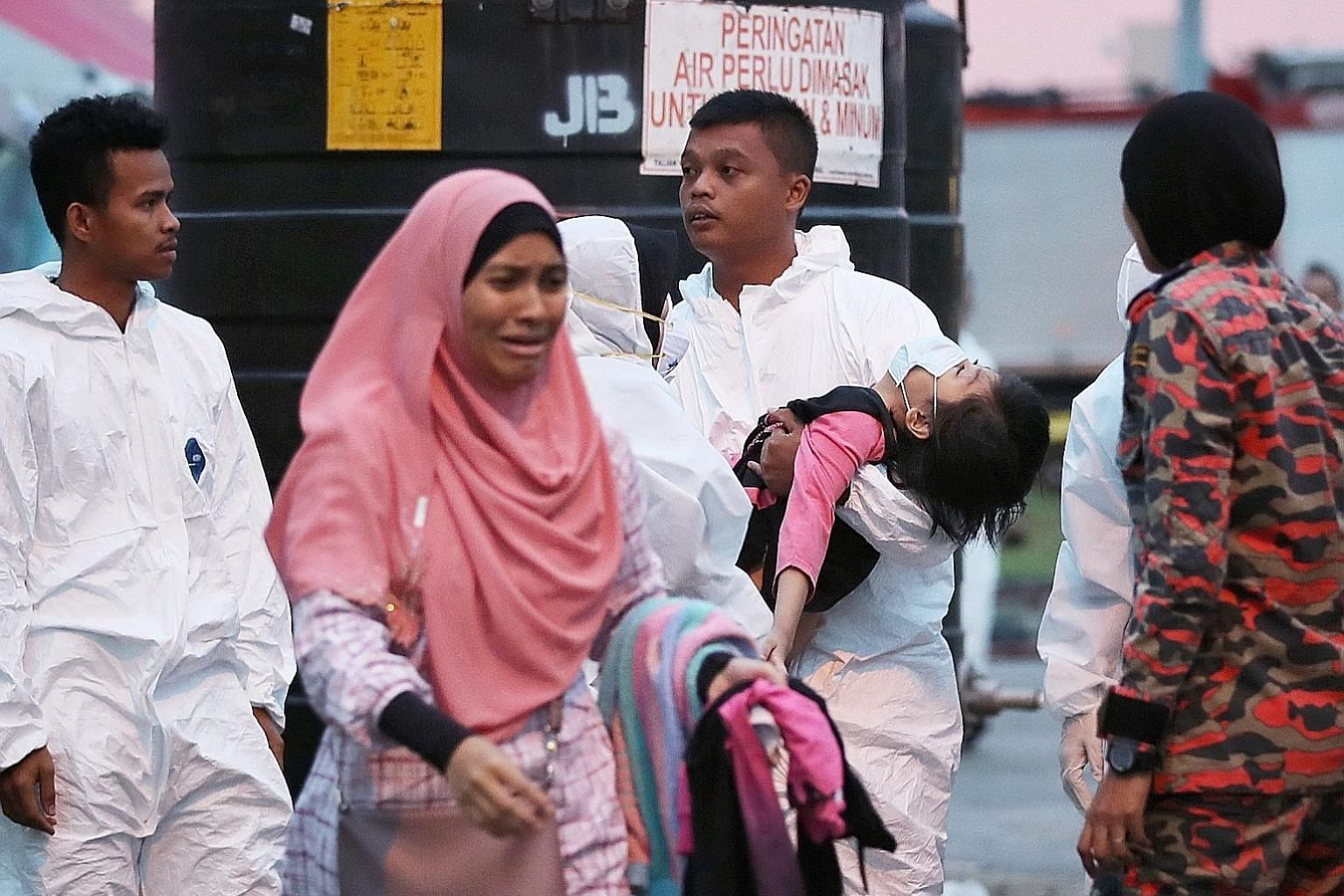A child being carried to an ambulance in Pasir Gudang last month. Schools in the area in Johor were shut after students reported breathing difficulties and vomiting that were believed to have been caused by air pollution.