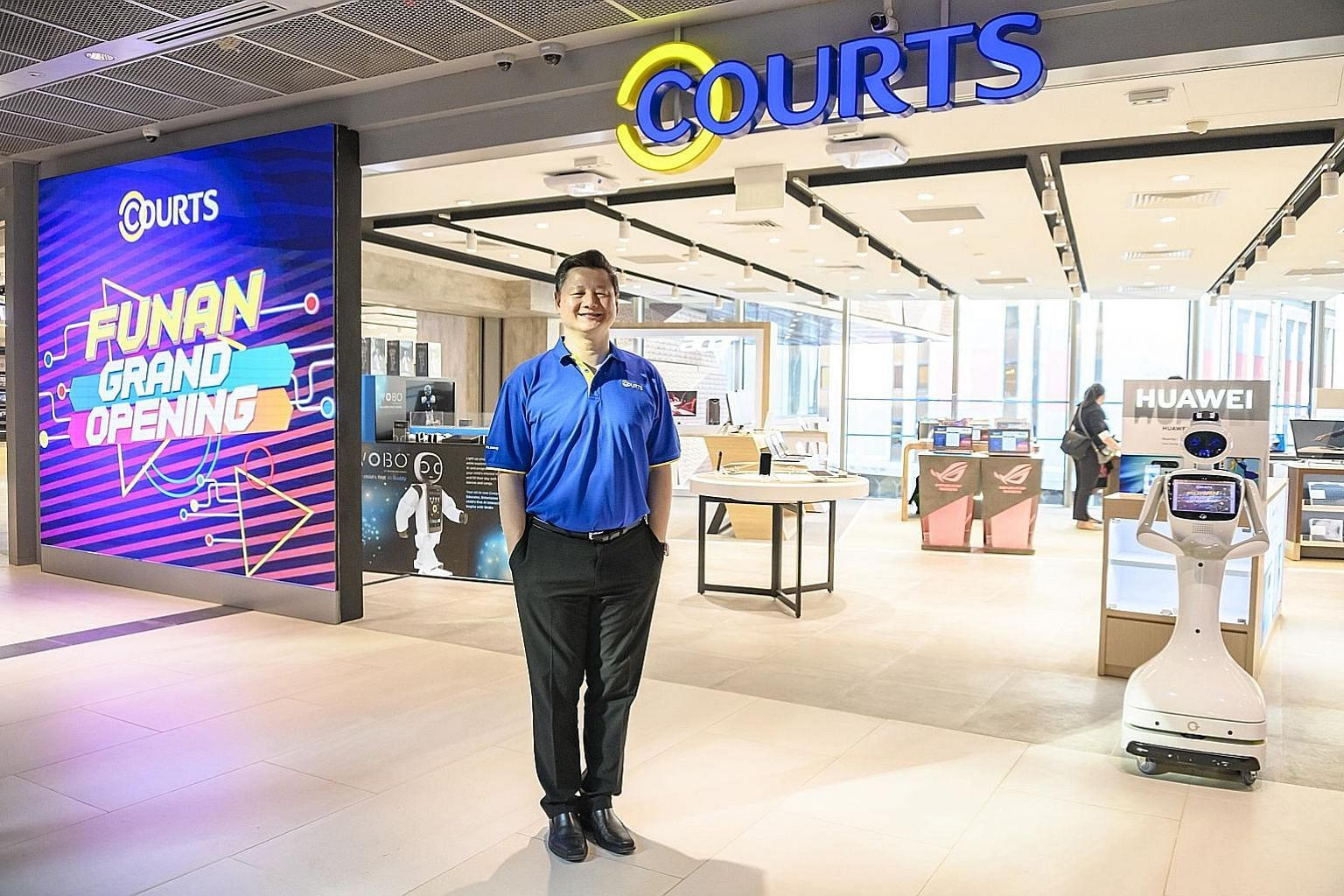 Courts Singapore chief executive Ben Tan at its new 12,000 sq ft store (left) in Funan mall, which houses a Google experience zone (right) as well as a Samsung smart home experience zone.