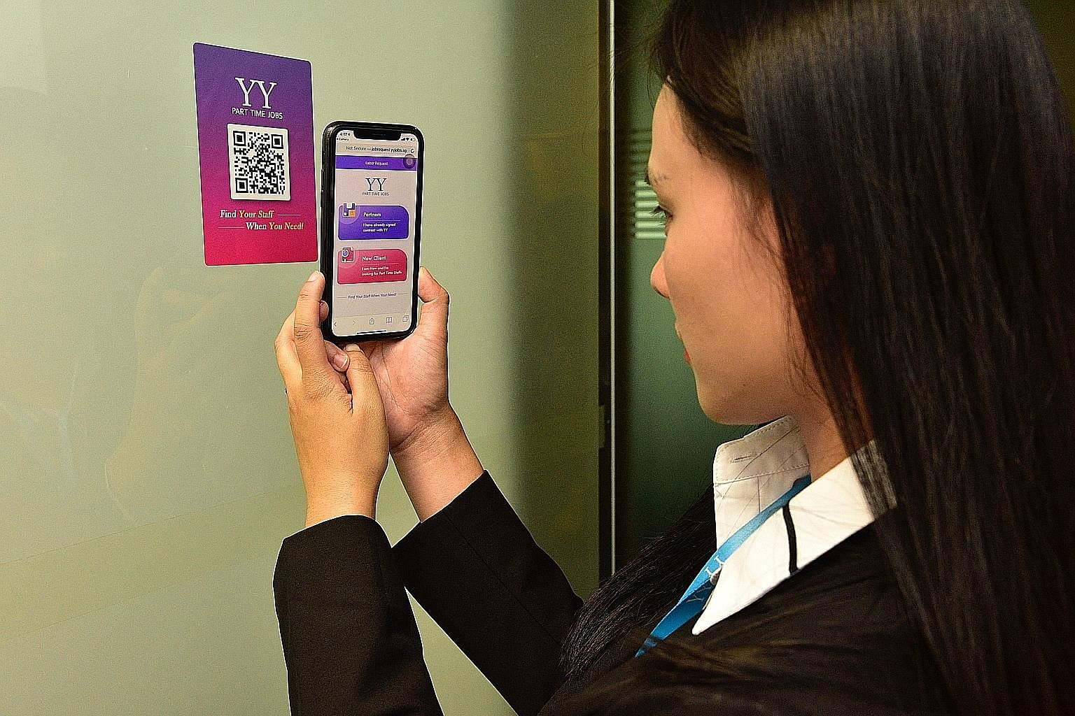 Ms Wendy Wang, IT manager from YY Hong Ye Group, scanning the company's QR code using the updated app in a demonstration yesterday.
