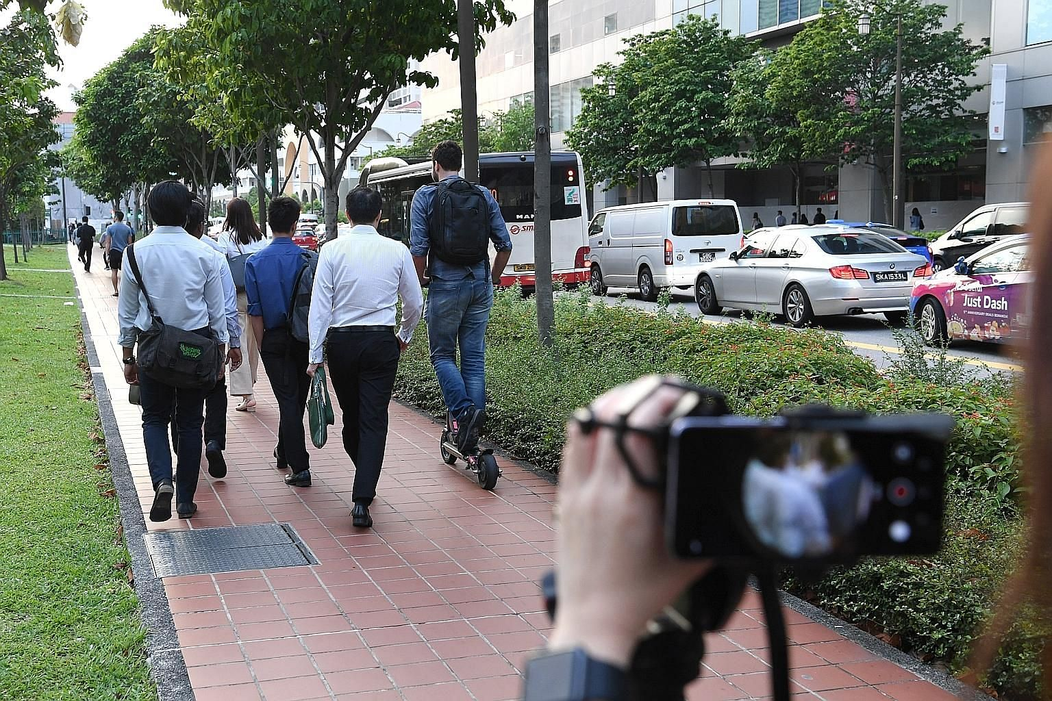 An ST journalist capturing the speed at which a PMD was travelling along Cross Street. ST PHOTO: KHALID BABA