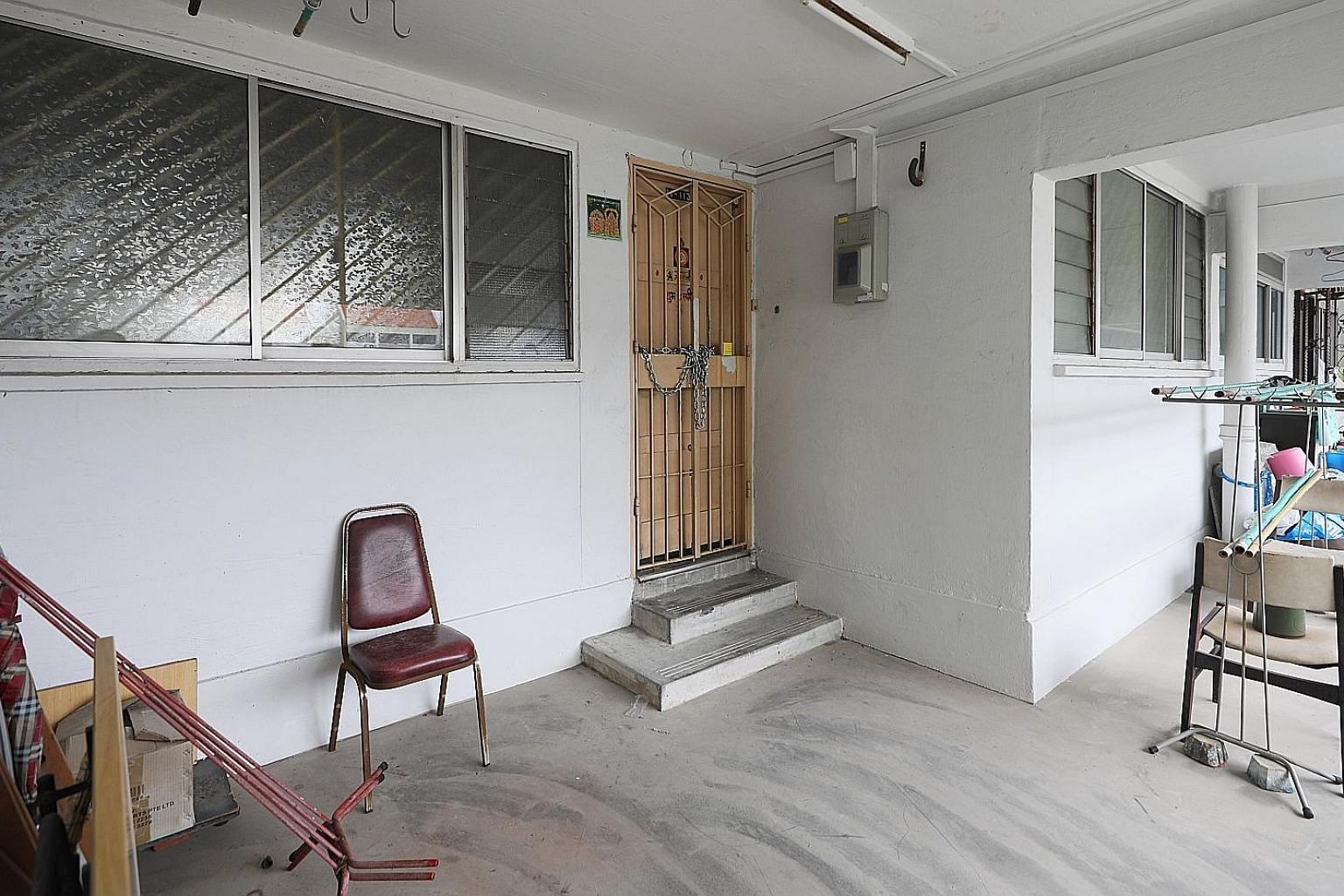 The police found the body of a man's mother in their flat (above) after he was found dead at the foot of their Housing Board block in Little India, where bloodstains (left) can be seen.