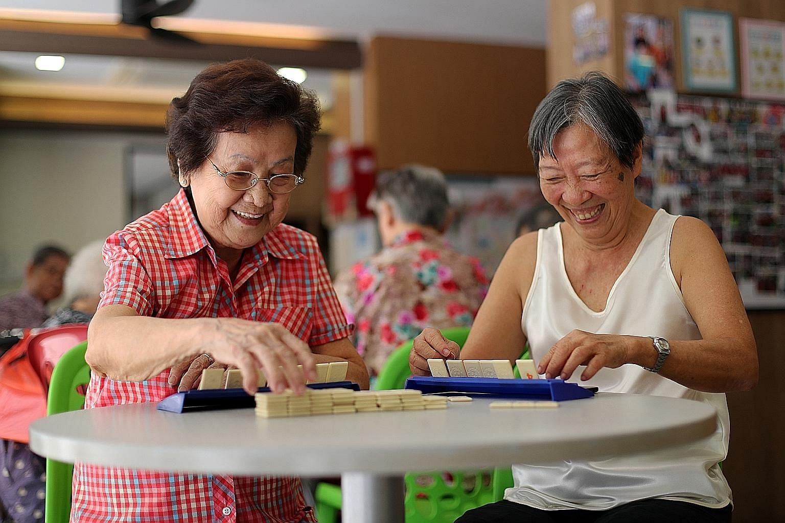 Madam Tsang Sow Kuen (in red) and Madam Tan Lu See having a game of Rummikub at the Wellness Kampung Senior Activity Centre on Thursday. For the two seniors, making their last wishes known - so their children know what to do when the time comes - is