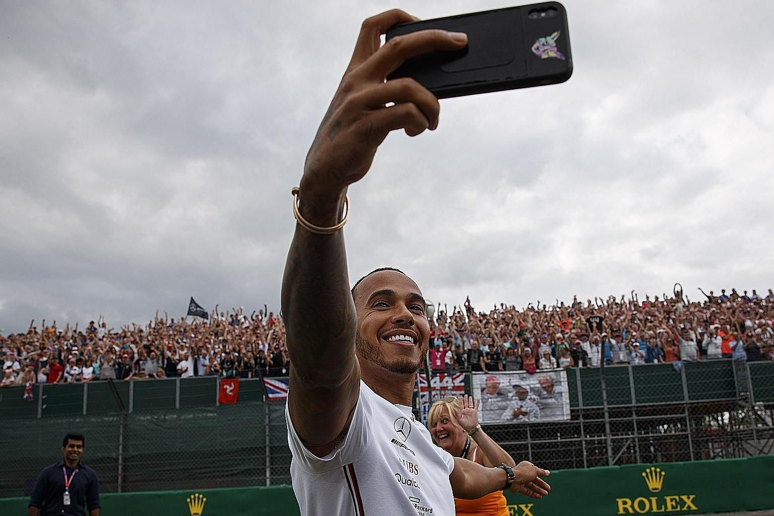 Five-time F1 world champion Lewis Hamilton taking a wefie with fans at Silverstone on Thursday. Tomorrow's British Grand Prix will clash with the Wimbledon men's singles final and the Cricket World Cup final in which England are going for their maide