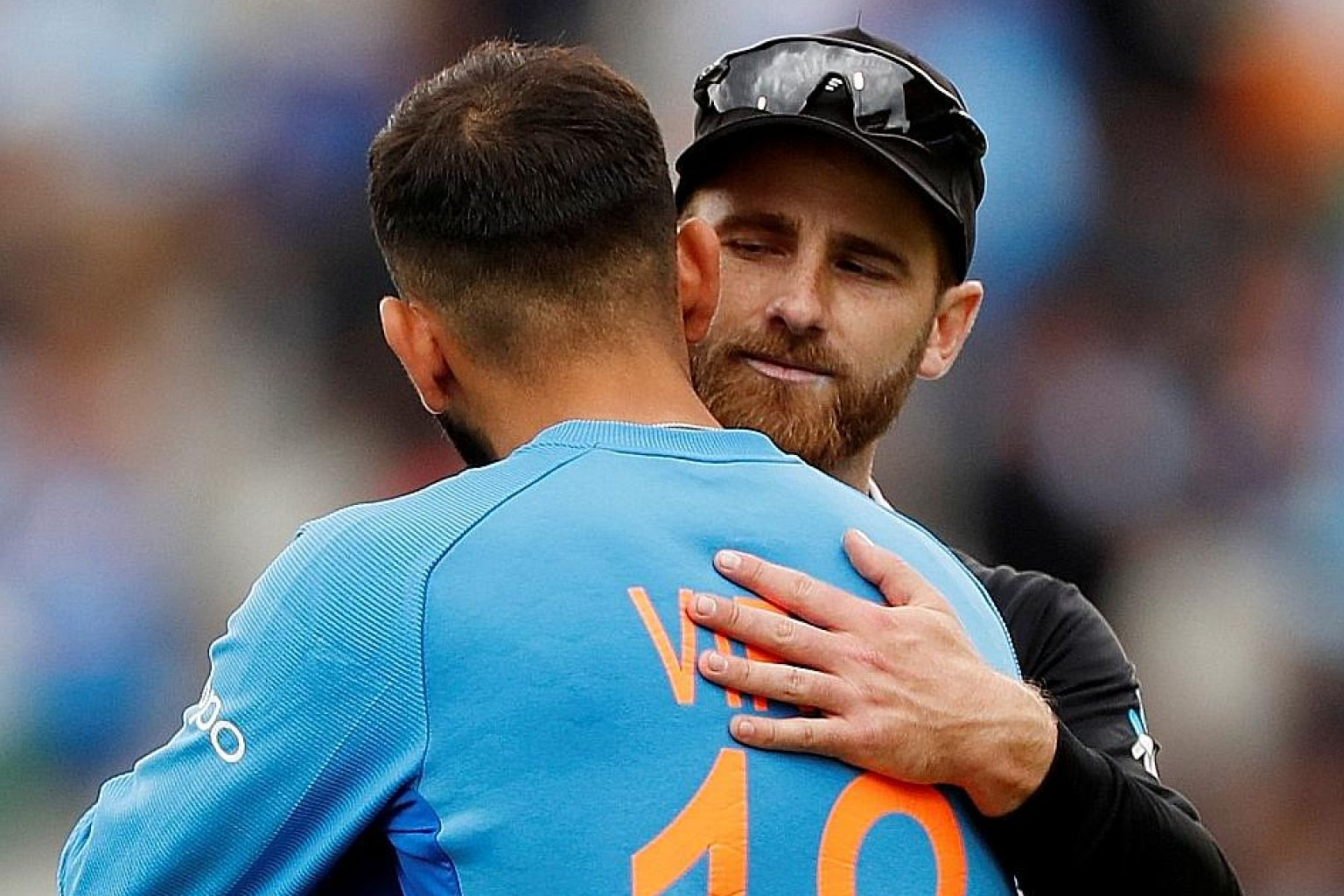 New Zealand captain Kane Williamson and his India counterpart Virat Kohli hug after the Black Caps won their rain-affected semi-final on Wednesday at Old Trafford by 18 runs. PHOTO: REUTERS