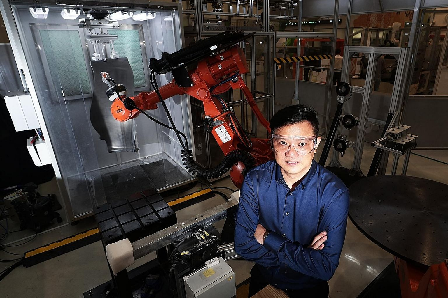 Mr Desmond Nyo, manager at KA Industrial Engineering, with a robot that automates spraying protective coatings on fan blades of aircraft engines. ST PHOTO: KELVIN CHNG