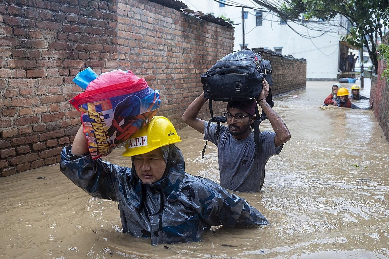 Police rescuing people yesterday from flooded houses following torrential rains in Kathmandu. In Nepal, 27 people have died in floods and landslides after heavy rains hit the country's eastern region and the southern plains.