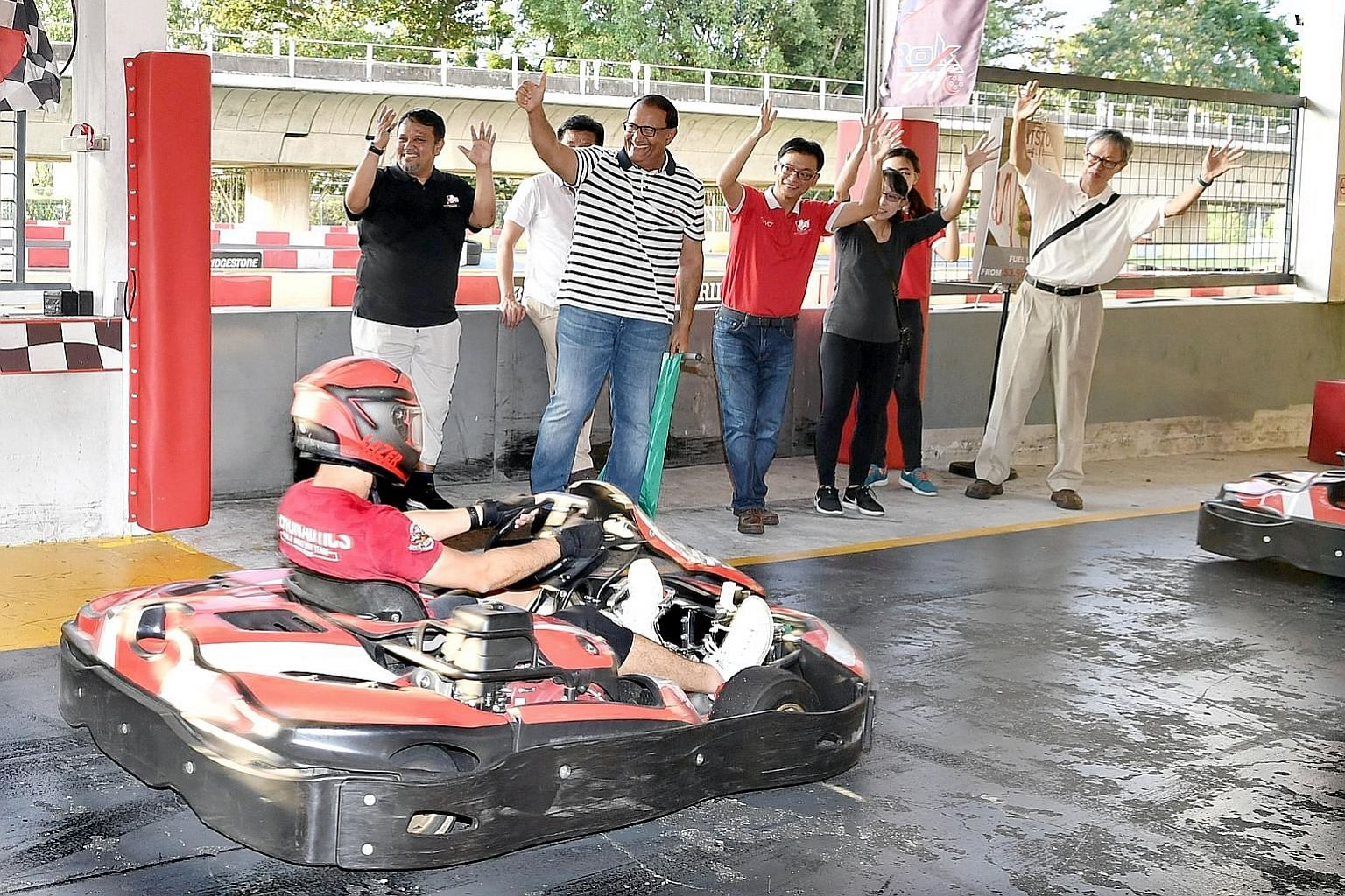 Minister for Communications and Information S. Iswaran (striped t-shirt) flagging off the karting race, one of the National Deaf Games events, at Kranji yesterday.