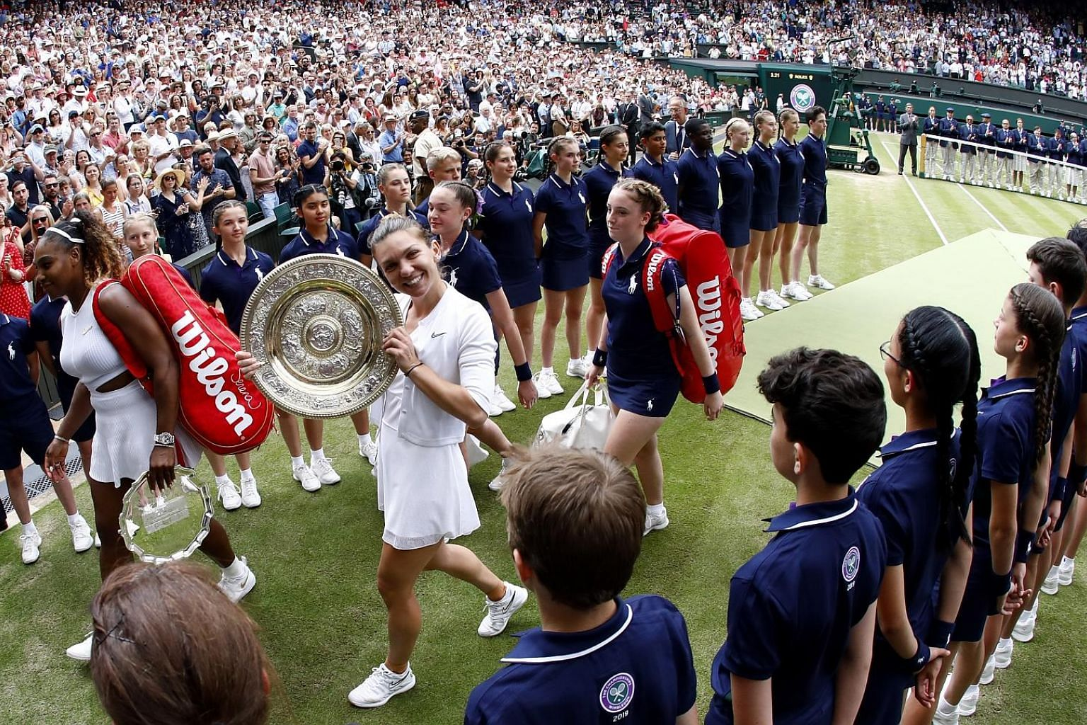 A beaming Simona Halep showing off the winner's Venus Rosewater Dish as she and losing finalist Serena Williams leave Wimbledon's Centre Court after the final yesterday. Halep's 6-2, 6-2 victory made her the first Romanian woman to win the Wimbledon title