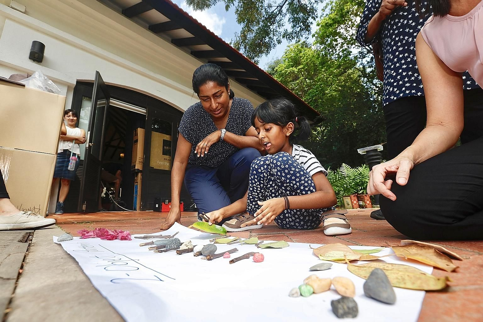 Mrs Shamala Ganessaraj watching as her six-year-old daughter Aarya formed patterns with pebbles, leaves and twigs - items collected from outdoors - at Fort Canning Park yesterday.