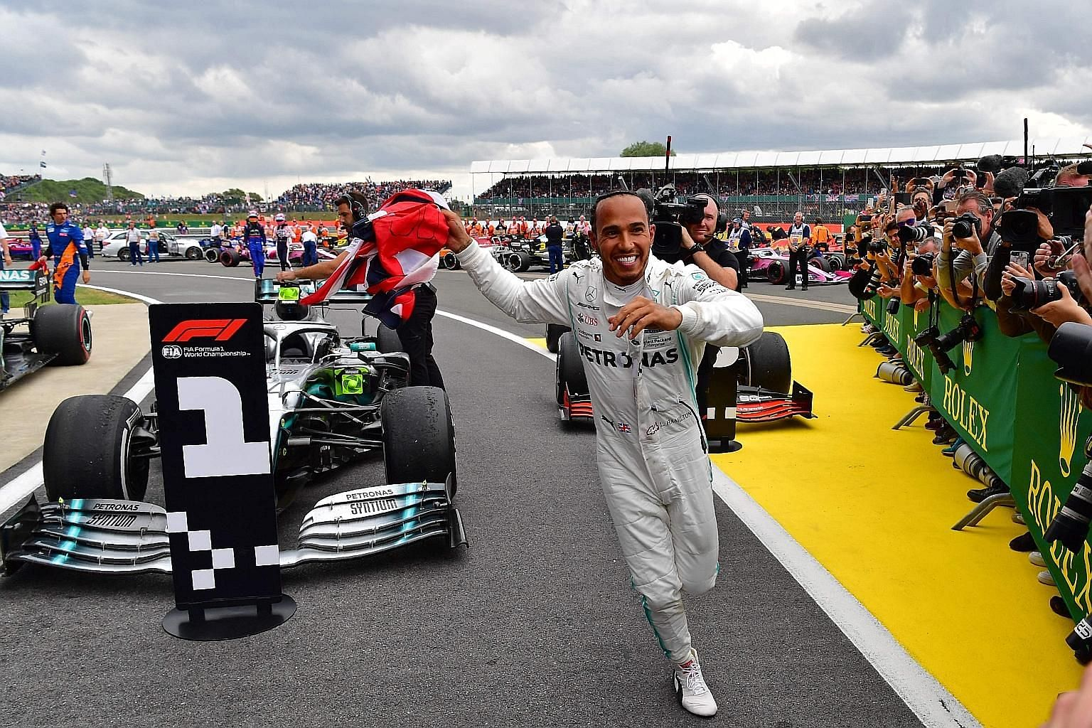 Lewis Hamilton running to celebrate with his team after winning the British Grand Prix at Silverstone yesterday. His Mercedes teammate Valtteri Bottas, who started on pole, looked set for victory until Hamilton pitted under the safety car and gained the a