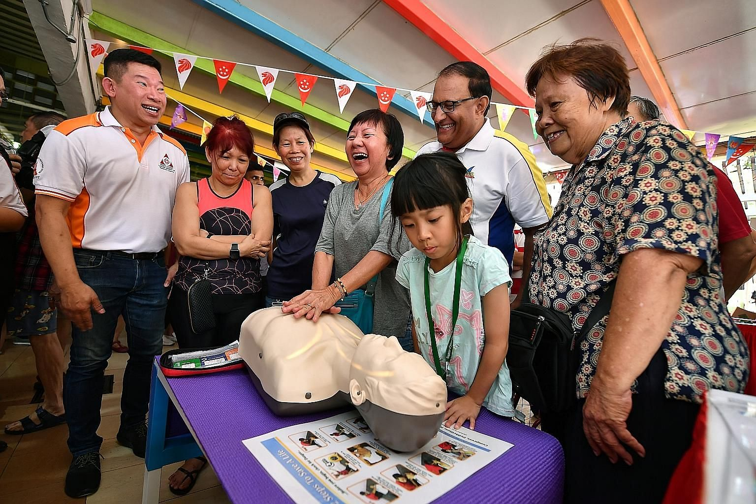 Above: Retiree Tan Boon Tien, 84, being taught how to use a fire extinguisher by members of the Singapore Civil Defence Force at a community event at West Coast Market Square yesterday. Right: West Coast GRC MP S. Iswaran watching people learn how to