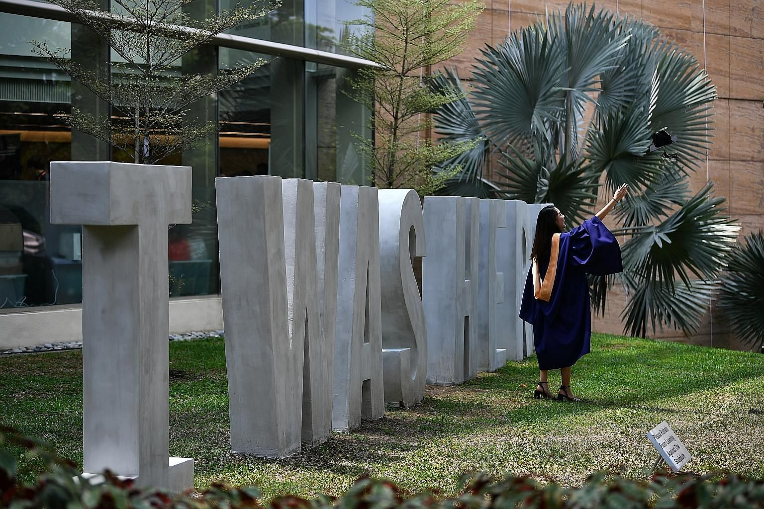 Above: Dr Arturo Neo says serving the underprivileged has taught him to empathise with patients. Left: A graduate taking photographs outside the NUS University Cultural Centre after yesterday's commencement ceremony.