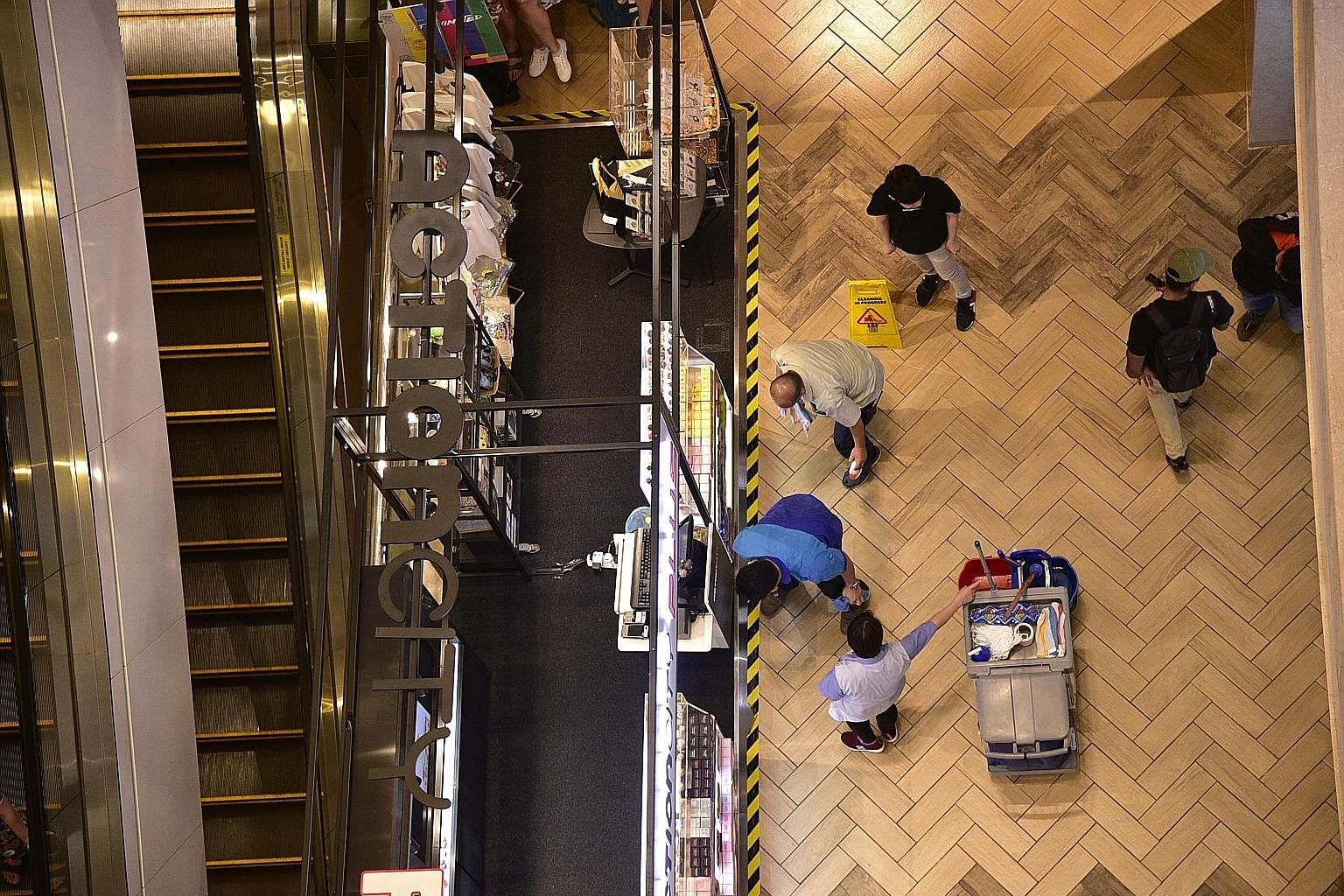 Workers cleaning up the area in basement two of Ngee Ann City, where the man landed after falling several floors. The 35-year-old died later of his injuries. ST PHOTO: DESMOND WEE