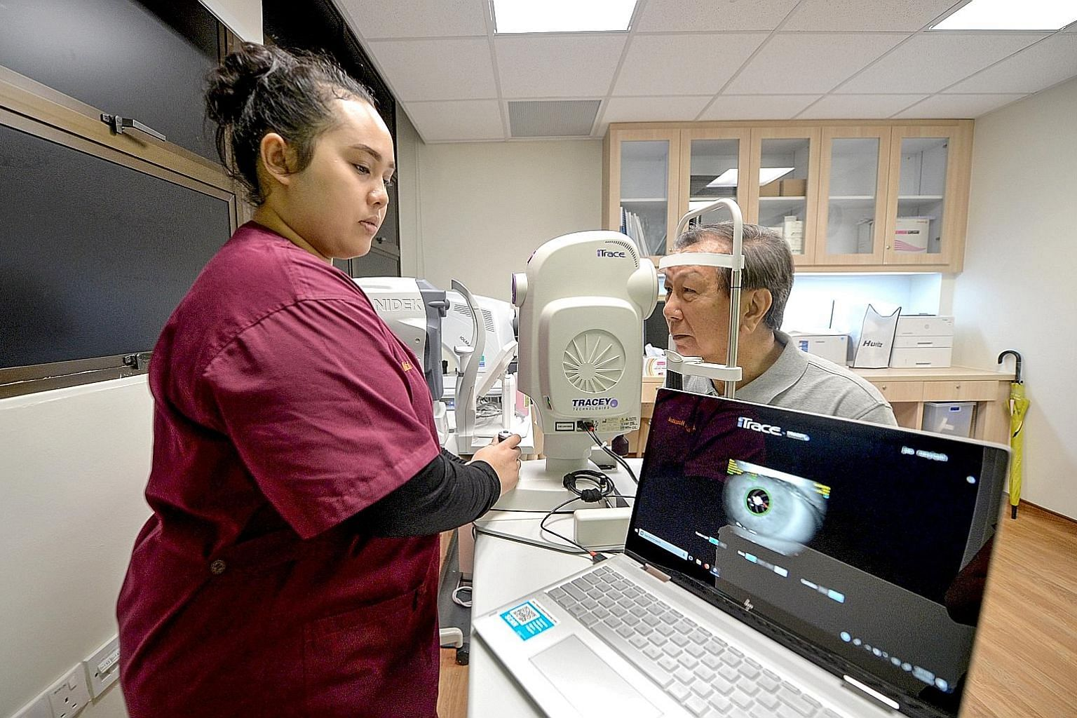 Clockwise from far left: Ophthalmic technician Nur Rasyiqah Jasmi, 25, assessing retiree Geoffrey Foo, 75, with an iTrace machine for the implant of special lenses for cataract patients with high astigmatism at Alexandra Hospital yesterday; Mr Foo at