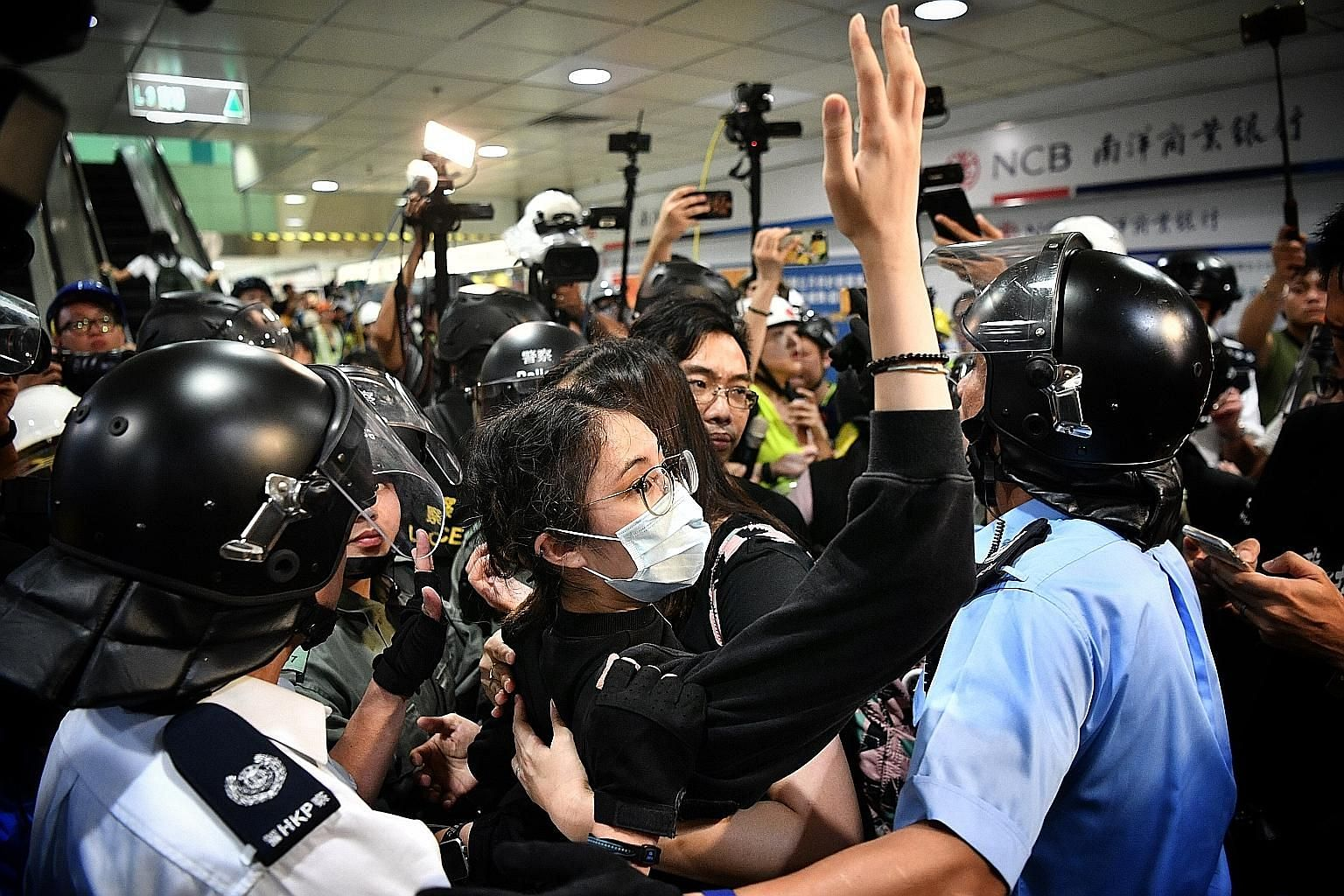 A young woman in a mask being taken away by the police at Lucky Plaza in Sha Tin on Sunday. Police arrested at least 40 people after the violence at New Town Plaza mall in the New Territories. The clashes left 28 injured, of which 11 were police offi