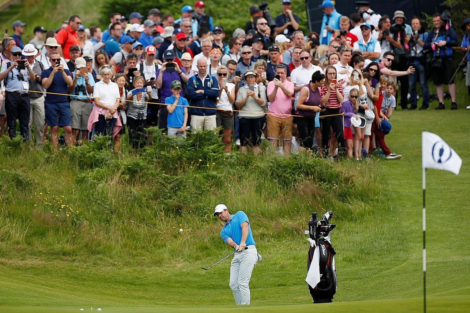 World No. 3 and home favourite Rory McIlroy watched by a sizeable crowd as he hits a chip during a practice session at Royal Portrush Golf Club in Northern Ireland yesterday.