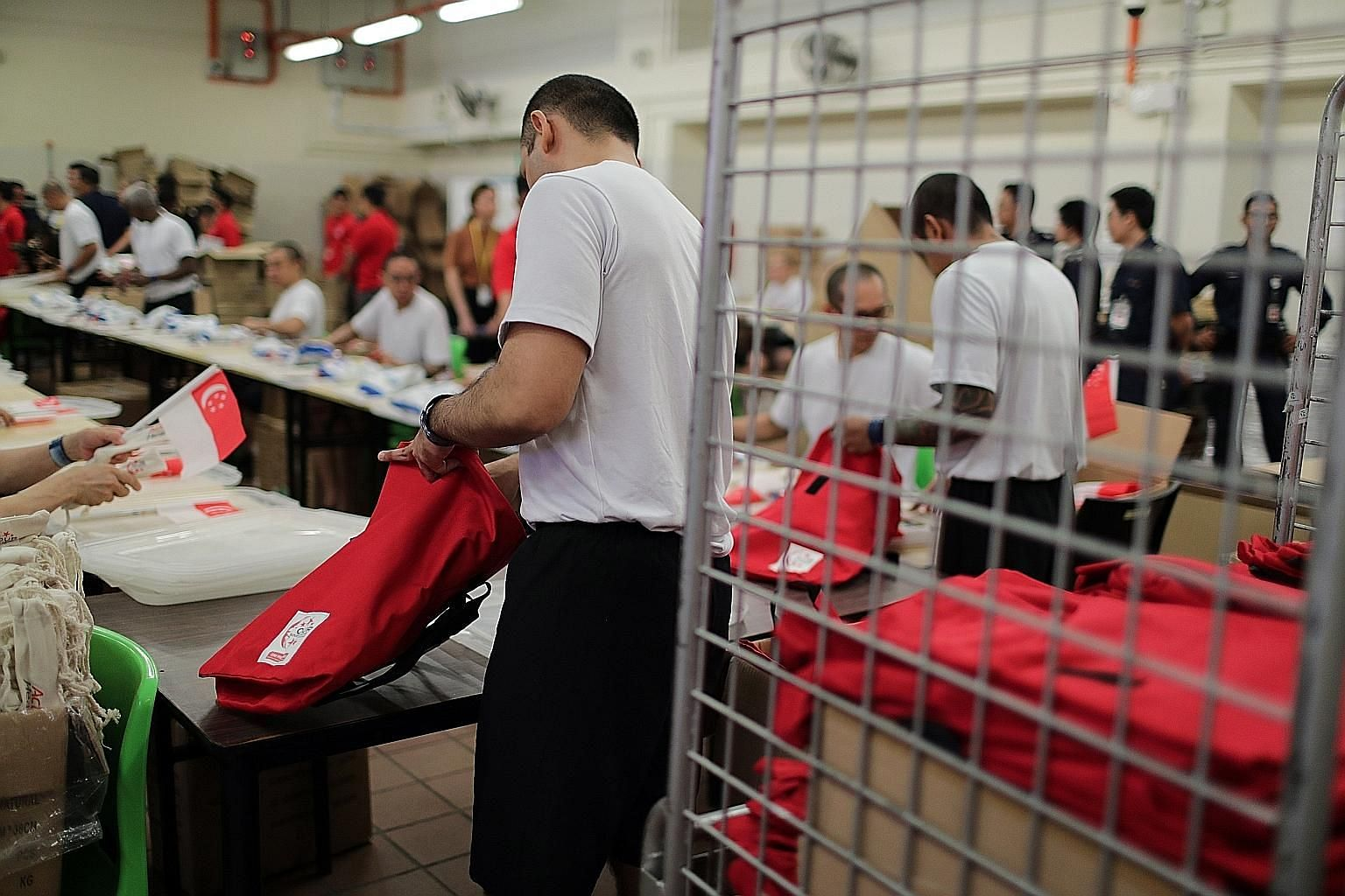 For the past three weeks, 30 Changi Prison inmates have been packing National Day Parade funpacks, as a way to give back to society. They volunteered for the project and are working to pack 50,000 funpacks by the end of this month. It is the first ti