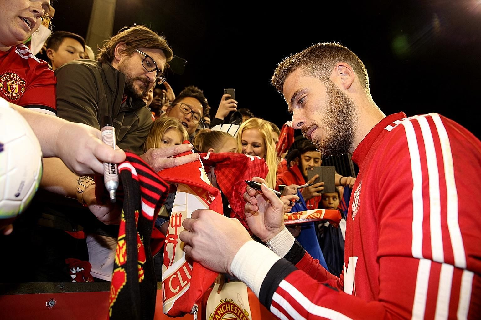 David de Gea signing autographs after a training session at the Perth Stadium last Thursday during Manchester United's pre-season tour. The goalkeeper is demanding to be among the best-paid players at the club.