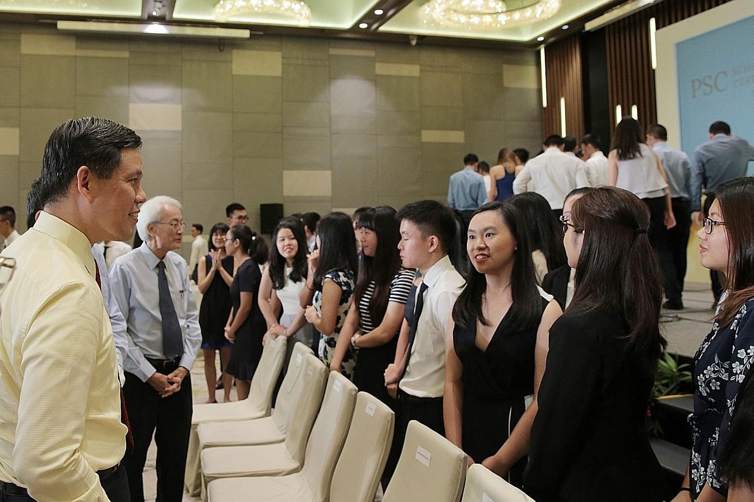 Mr Chan Chun Sing, who is Minister-in-charge of the Public Service, chatting with scholarship recipients at yesterday's Public Service Commission Scholarships Award Ceremony at Parkroyal on Beach Road hotel.