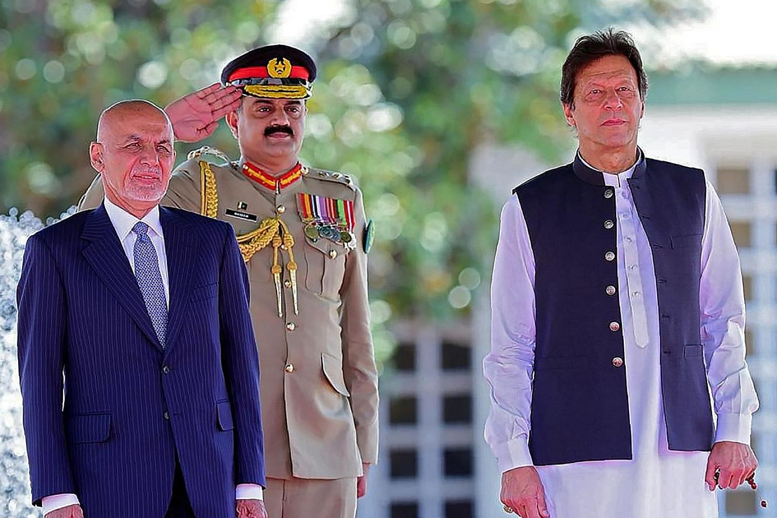 Visiting Afghan President Ashraf Ghani (left) and Pakistani Prime Minister Imran Khan (right) reviewing an honour guard during a welcome ceremony in Islamabad last month. PHOTO: AGENCE FRANCE-PRESSE