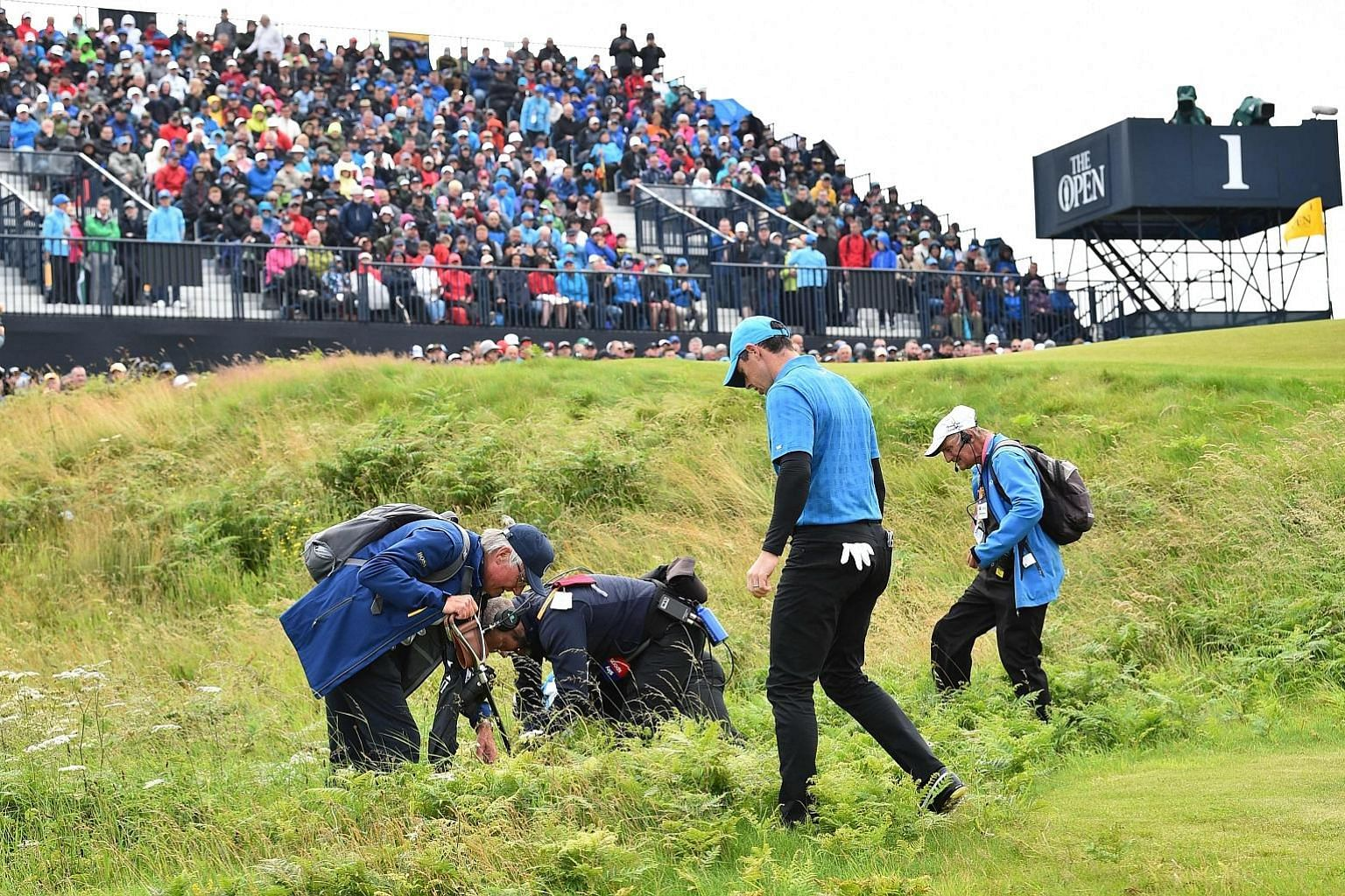 Rory McIlroy searching for his ball after he hooked his tee shot out of bounds at the first hole in the first round of the British Open at Royal Portrush Golf Club yesterday.