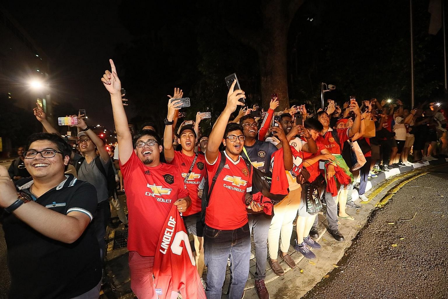 Above: Manchester United midfielder Paul Pogba, who has been linked with a move away from Old Trafford, was the centre of attention as the Frenchman stepped off the bus at The Ritz-Carlton, Millenia Singapore last night. Left: Diehard United fans lin