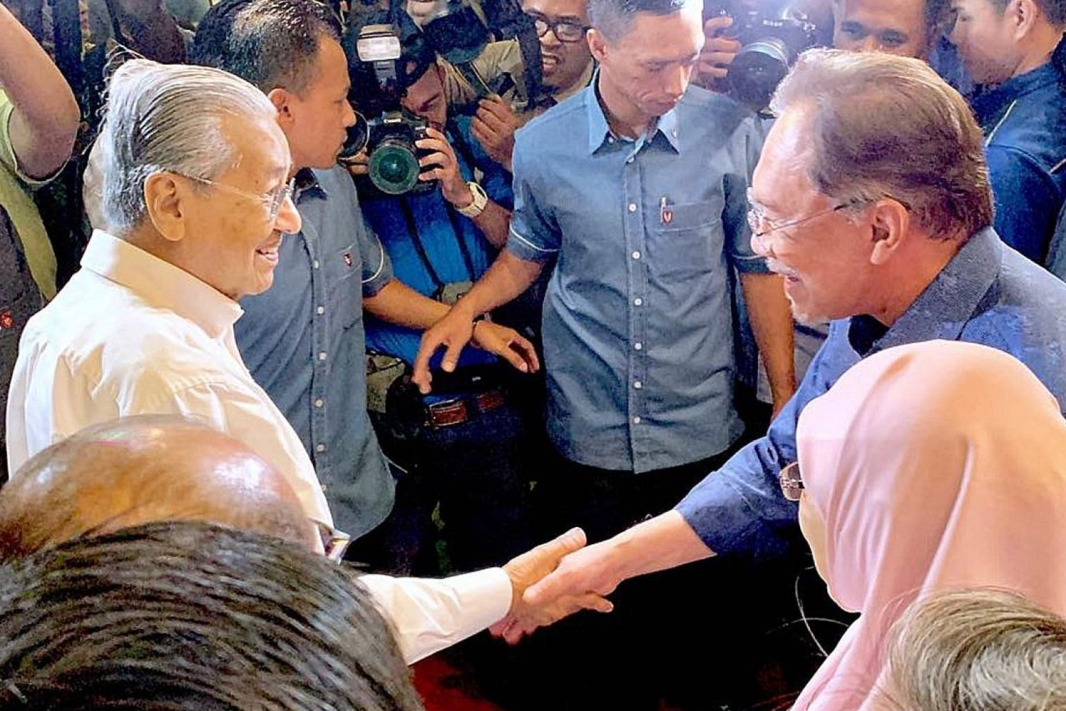 Malaysian Prime Minister Mahathir Mohamad (left) being greeted by Parti Keadilan Rakyat president Anwar Ibrahim on arrival at the party's retreat in Port Dickson yesterday. ST PHOTO: SHANNON TEOH