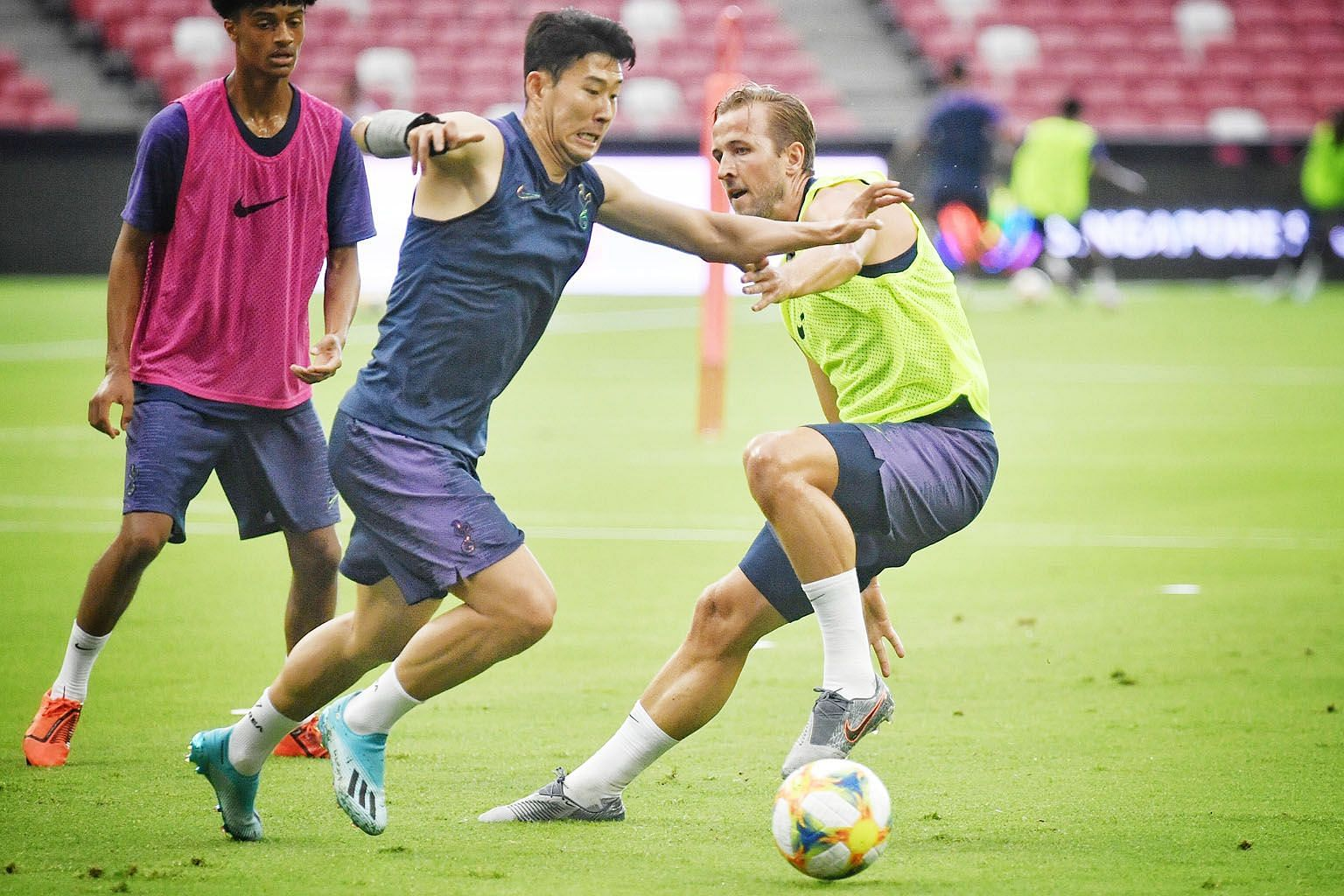 Tottenham captain Harry Kane challenging fellow forward Son Heung-min for the ball during their training session at the National Stadium yesterday. ST PHOTO: CHONG JUN LIANG