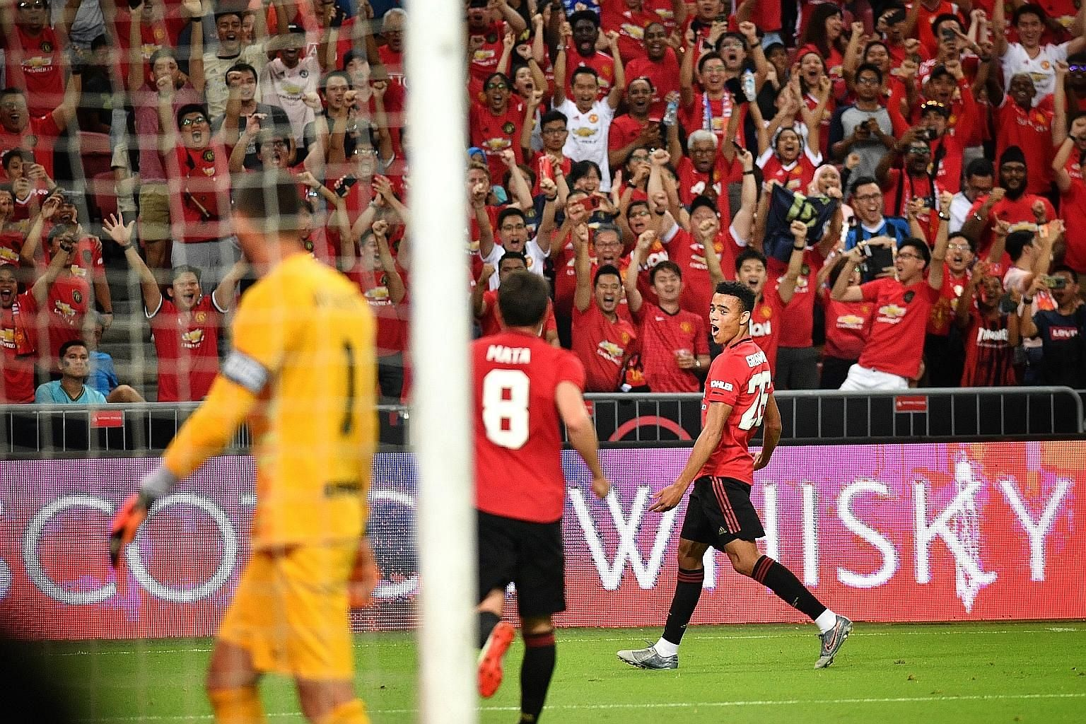 Manchester United's Mason Greenwood (right) celebrating after scoring the only goal of the game against Inter Milan at the National Stadium last night. The match attracted a sold-out crowd of more than 52,000.