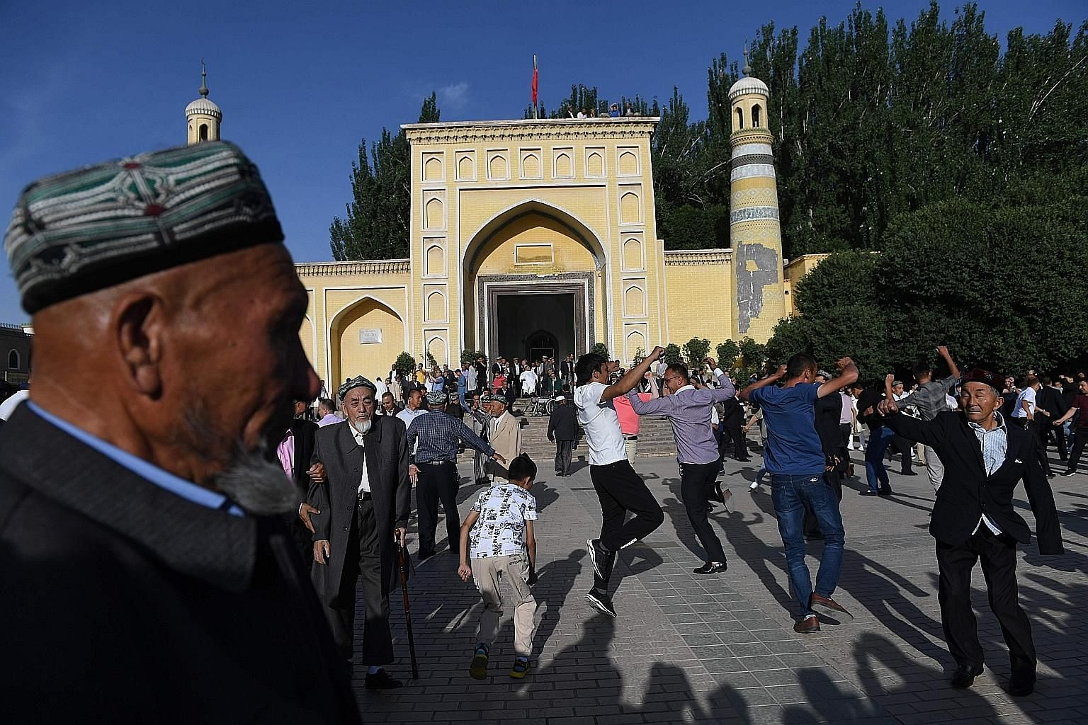 Uighur men dancing outside a mosque in Kashgar, in China's western Xinjiang region, after prayers last month marking the end of Ramadan. The region is tightly controlled by the Chinese authorities.