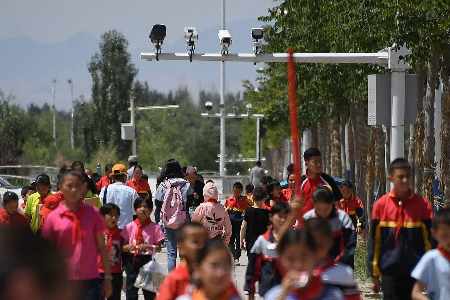Schoolchildren walking below surveillance cameras in Akto, in China's western Xinjiang region. In China, surveillance is becoming pervasive, and algorithms score citizens on their behaviour. The writer says it has been argued that if the West enacts