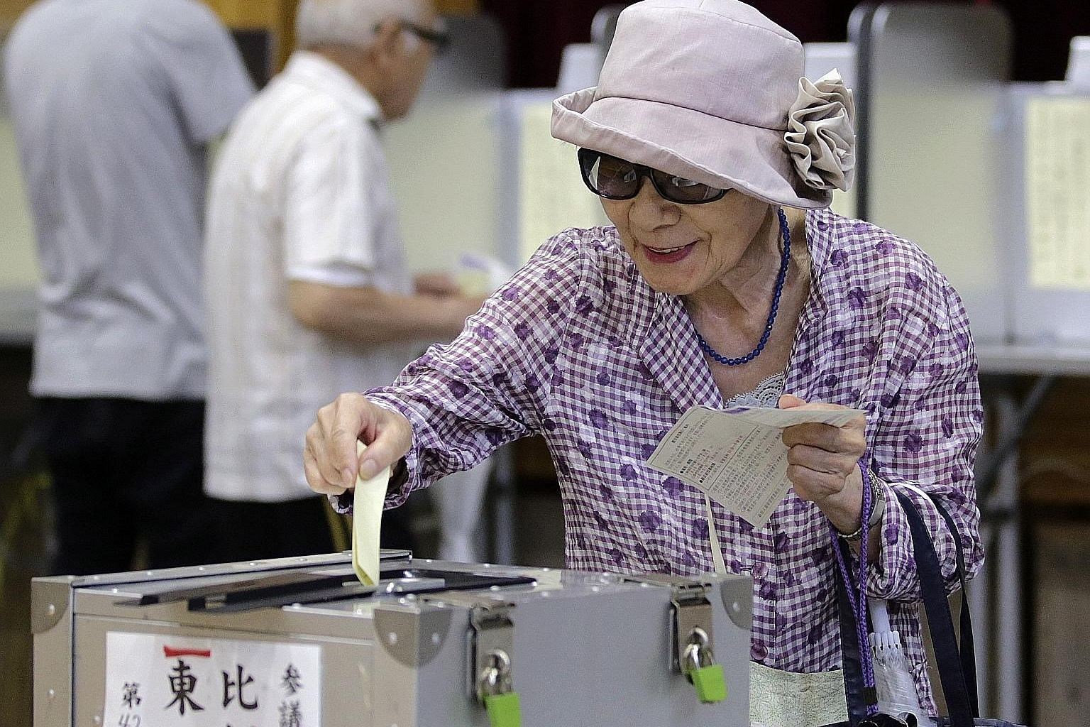 A Japanese voter casting her ballot at a polling station in Tokyo yesterday. Voter turnout is expected to fall under 50 per cent for the first time since 1995 amid public apathy, despite some businesses closing stores to allow staff to vote and eater