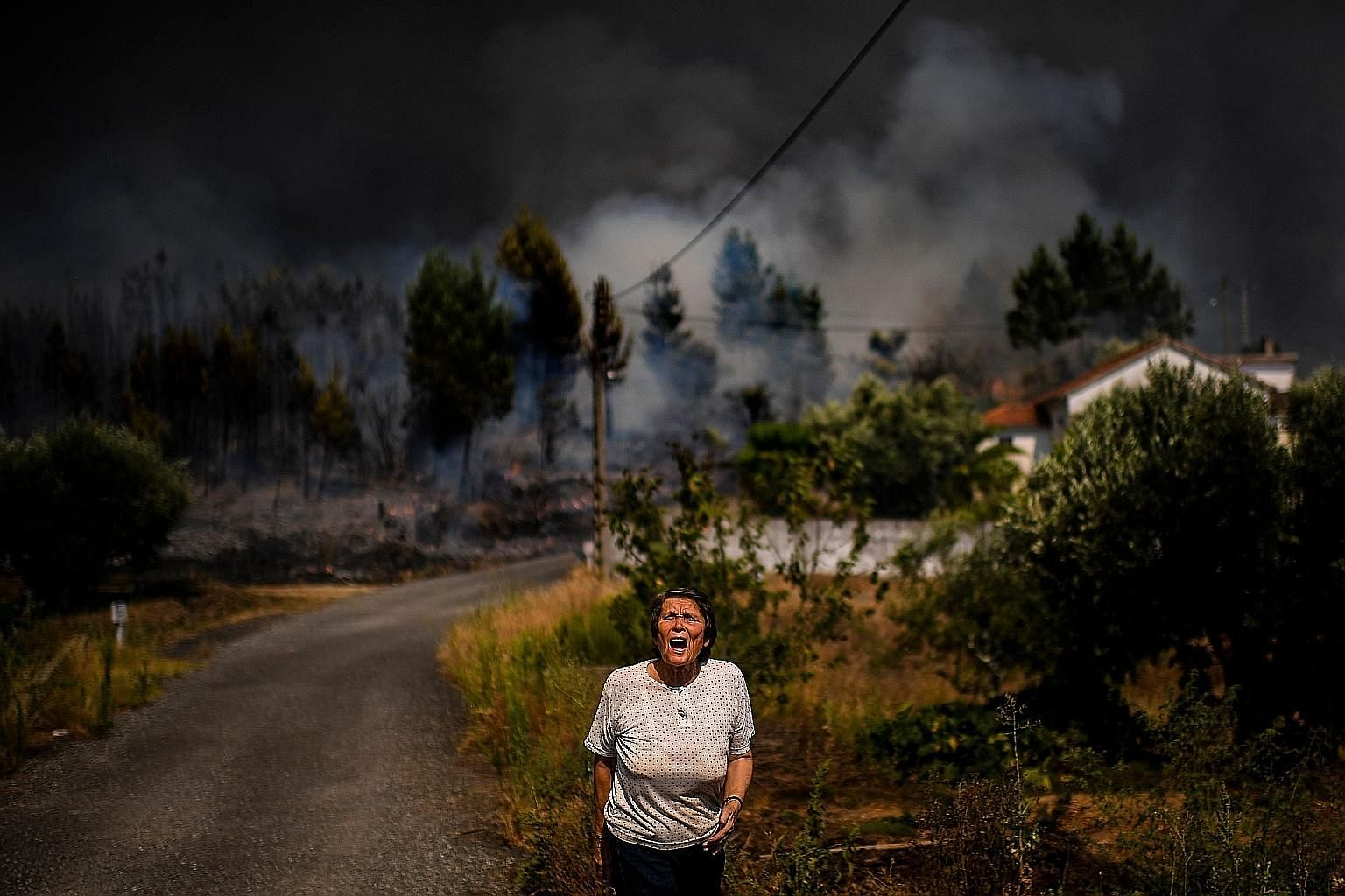 A villager shouting for help as a wildfire approached a house at Casas da Ribeira village in Macao, central Portugal, on Sunday. Fires that swept the mountainous region for nearly 48 hours were under partial control yesterday, but adverse weather con