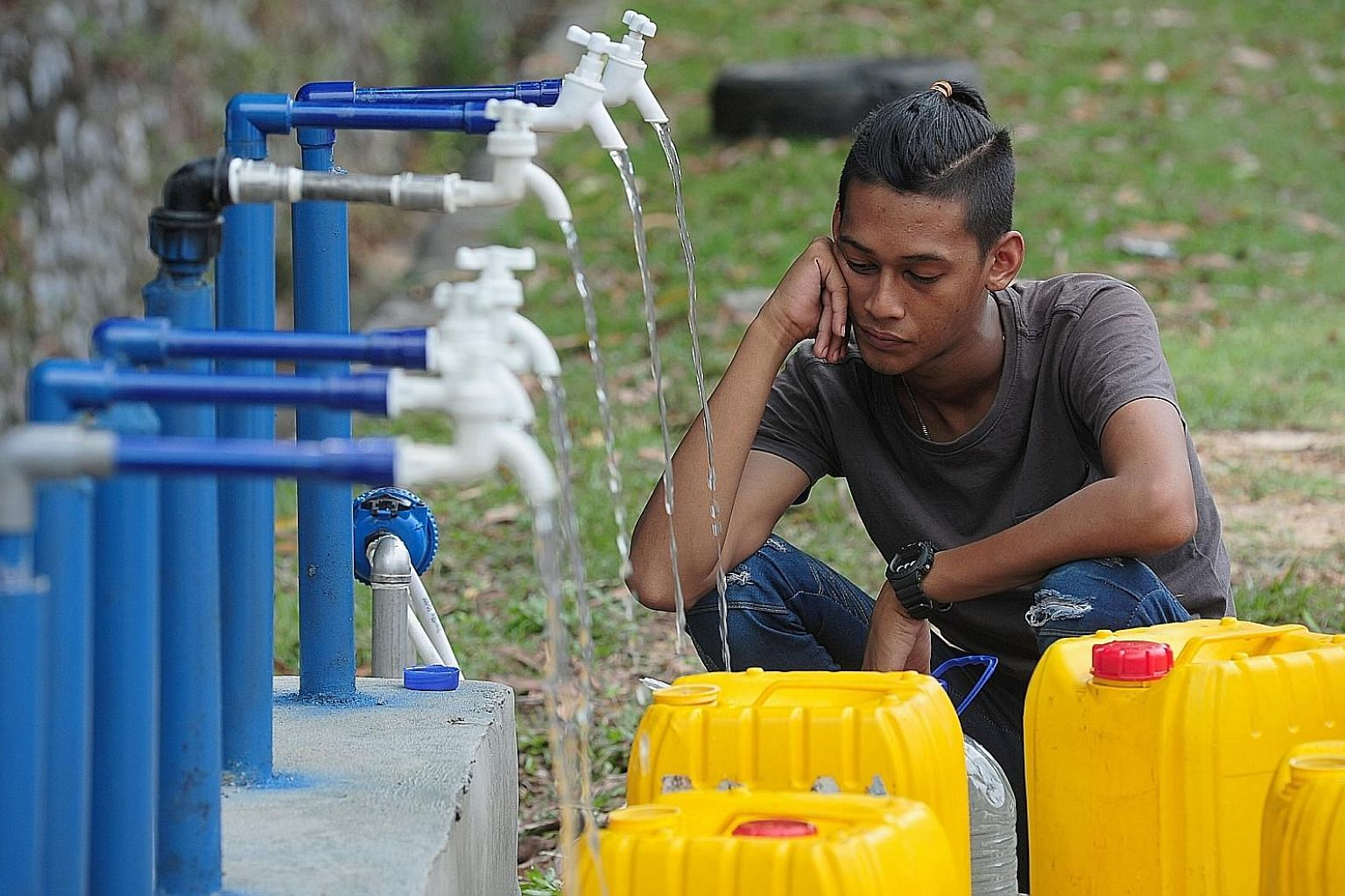A man filling up his containers with water from pipes yesterday, after supply was cut off in Selangor. Millions of consumers like him were affected by the second water outage in days. PHOTO: BERNAMA
