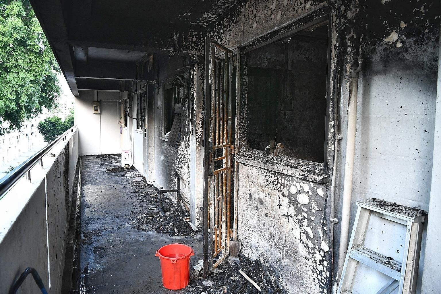 The corridor outside the fourth-floor unit in Block 224 Ang Mo Kio Avenue 1 that was gutted in the fire yesterday. The SCDF rescued one adult and three children from the unit next to the flat. Around 60 people from the block were also evacuated. This