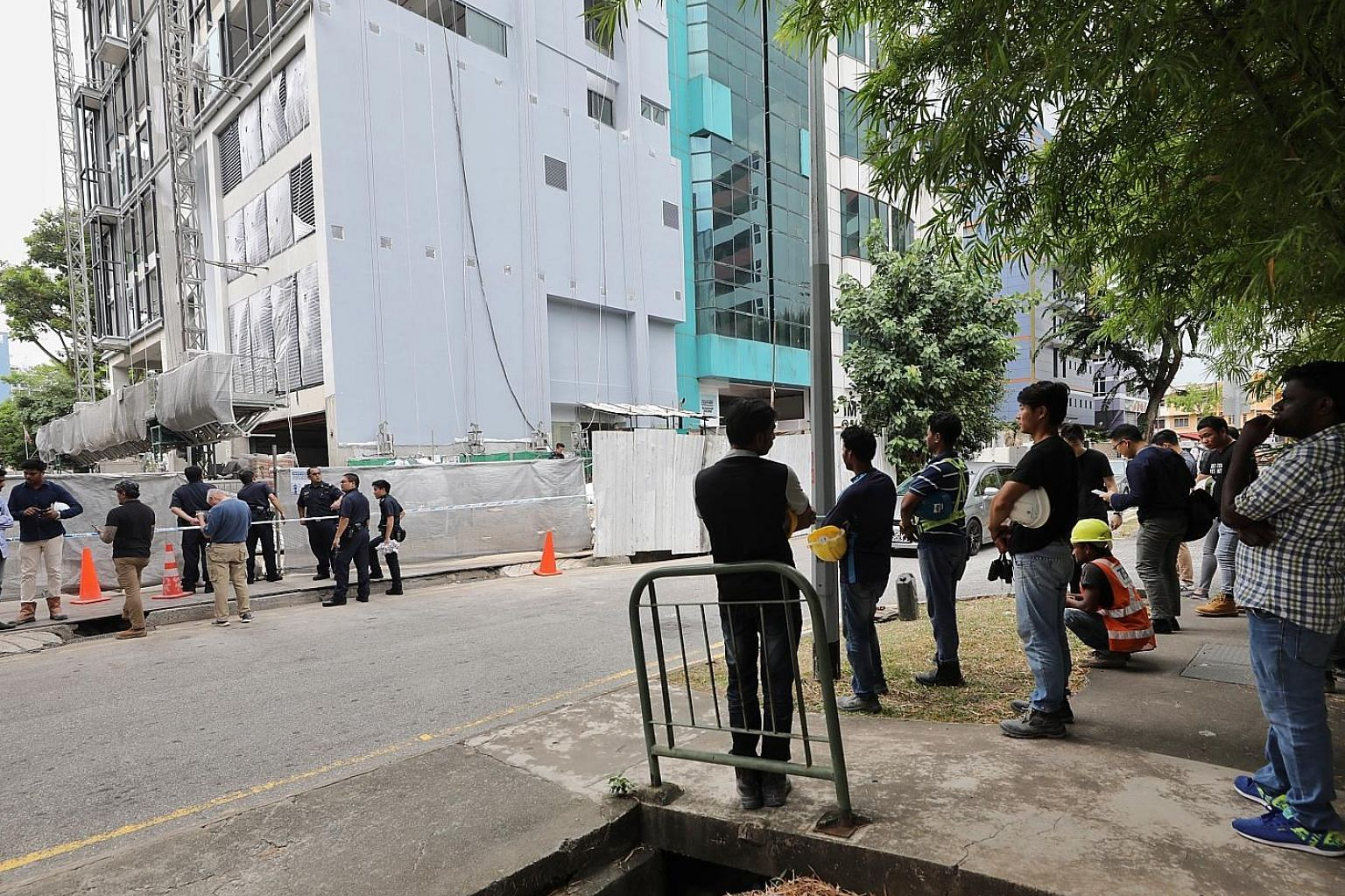 Above: The area where a suspected World War II bomb was found, on the grounds of a half-constructed building in Geylang Lorong 23, was cordoned off after its discovery yesterday. The safety officer of the construction site confirmed that the object w