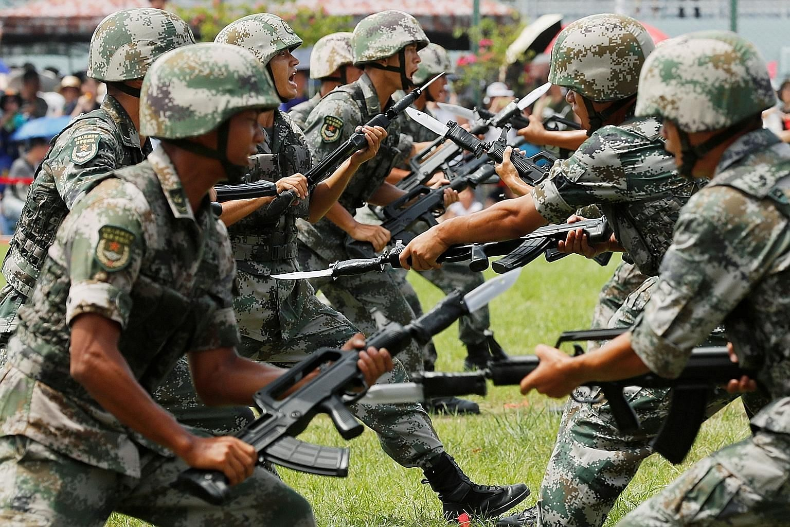People's Liberation Army (PLA) soldiers taking part in a performance during an open day at the Stonecutters Island naval base in Hong Kong last month. In its defence White Paper issued yesterday, China said the PLA had an important role in protecting