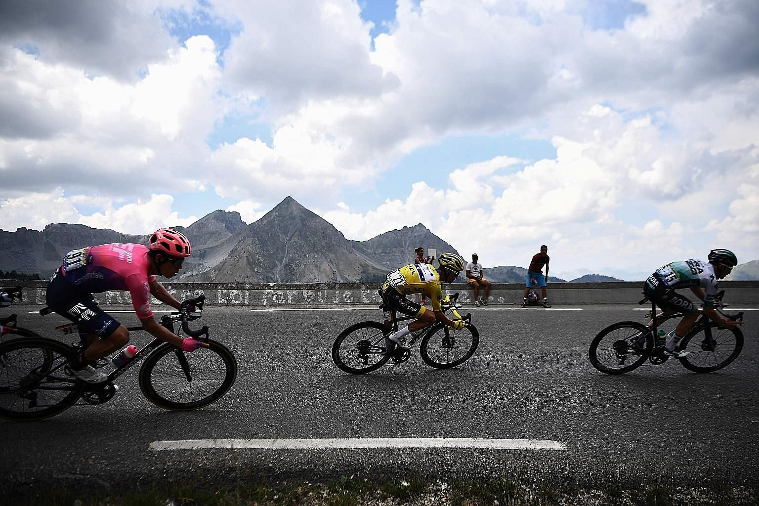 Julian Alaphilippe, in the yellow jersey, is sandwiched between Rigoberto Uran (left) and Gregor Muhlberger on a curve during the 18th stage of the Tour yesterday. PHOTO: AGENCE FRANCE-PRESSE