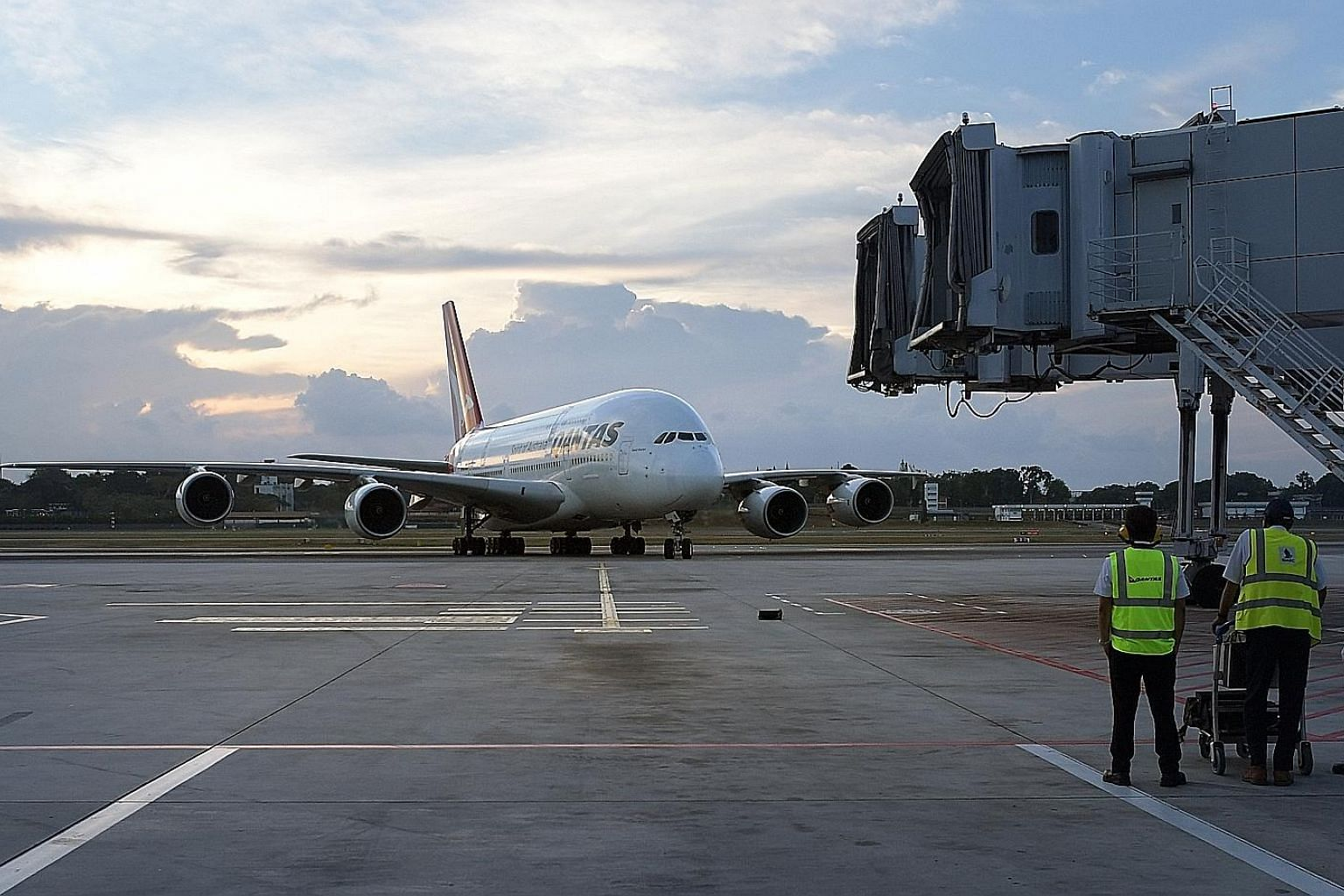 SIA Engineering technicians standing by as a plane pulls into Changi Airport. The company says it has begun to note improvement in manpower utilisation, productivity and turnaround time from its transformation initiatives and adoption of technologies