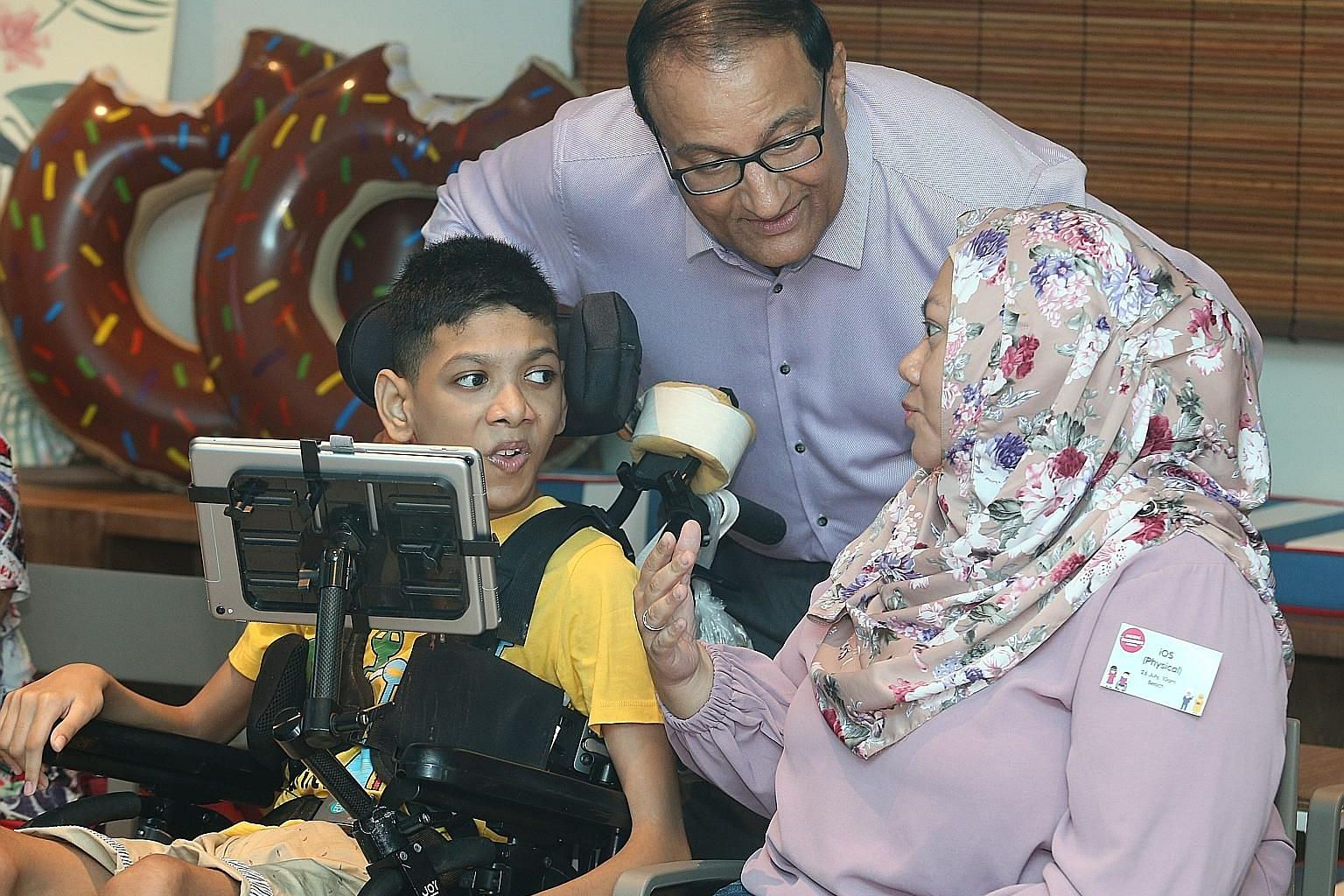 Madam Siti Fadillah Mohamed Noor, 41, and her son Muhammad Sayfullah Mohamad Sahrin, 16, chatting with Minister for Communications and Information S. Iswaran at the Digital Inclusion Festival yesterday. The teenager, who has quadriplegic cerebral palsy, a