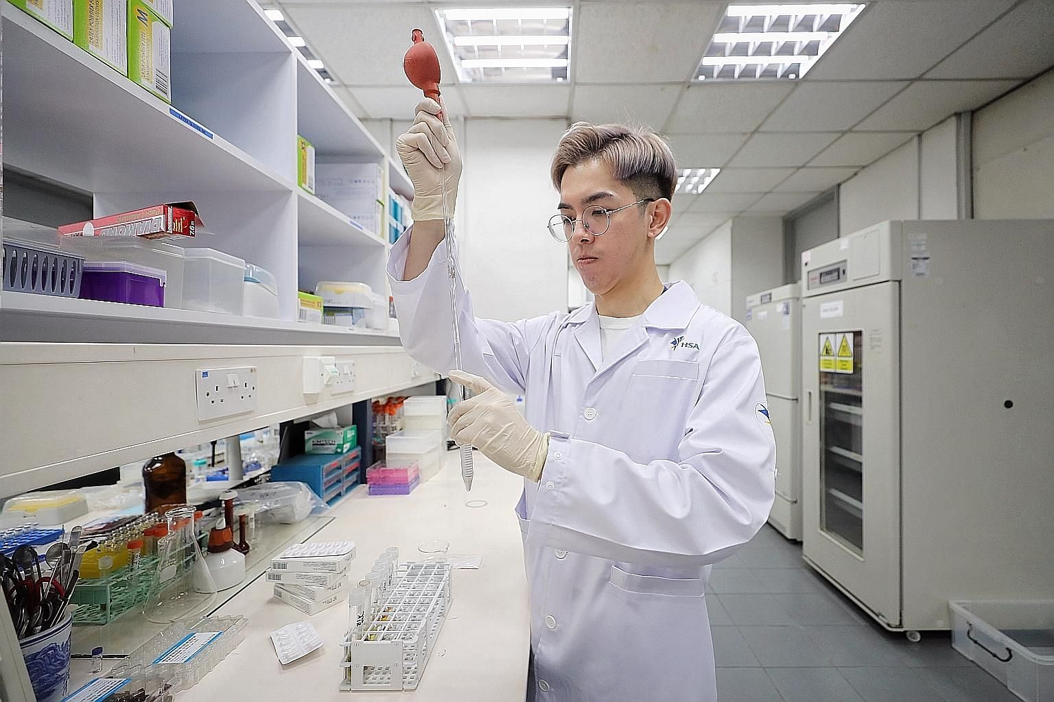 Senior laboratory officer Edwin Hoi adding solvents to crushed losartan tablets at the Health Sciences Authority. Three brands of the drug were taken off the market at the end of March as they contained unacceptable amounts of impurities that, taken