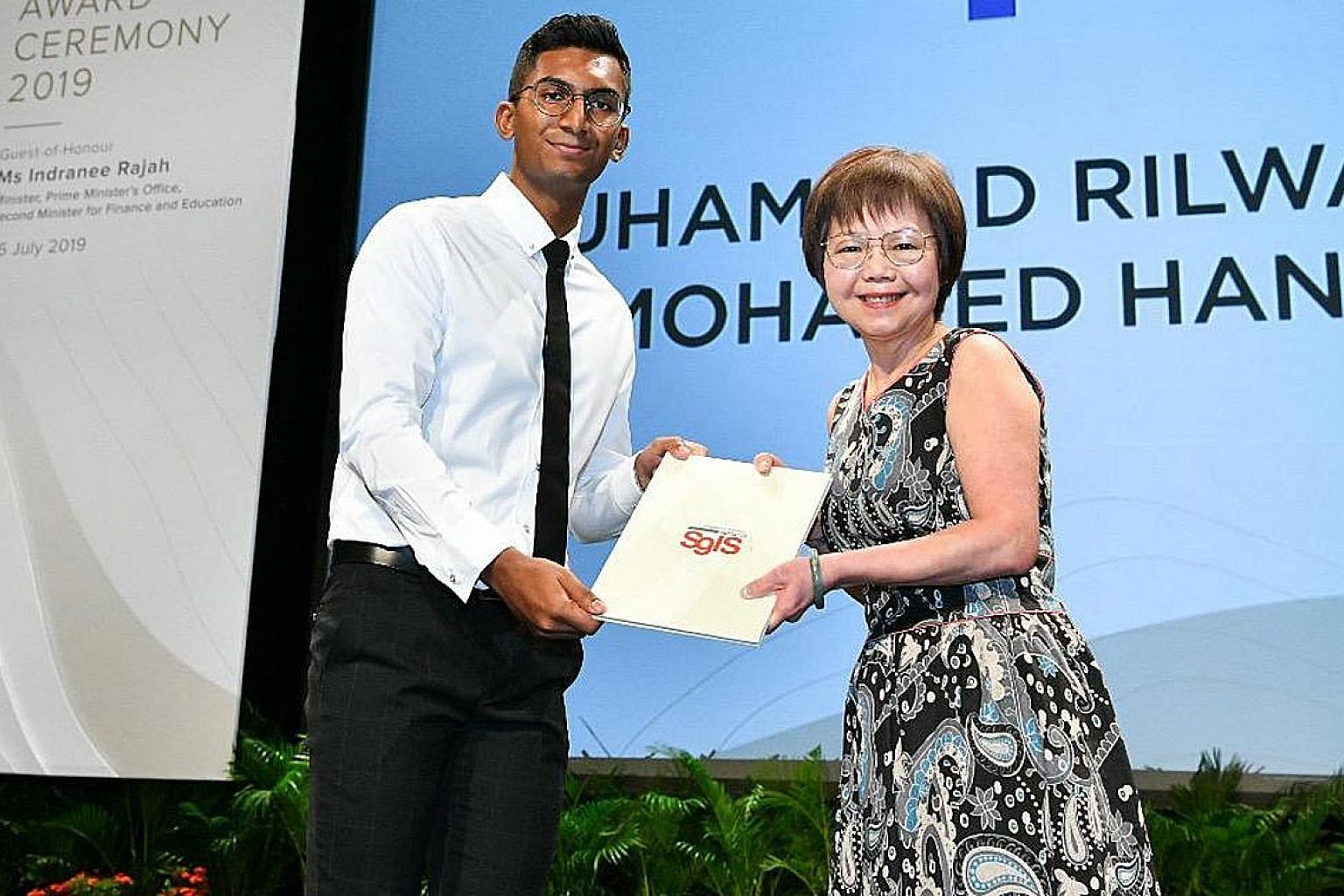 Mr Muhammad Rilwan Mohamed Haniffa receiving his Singapore-Industry Scholarship (SgIS) award from Ms Ingrid Lim, assistant vice-president of human resources at Singapore Press Holdings. The 20-year-old received a full-term SgIS with SPH.