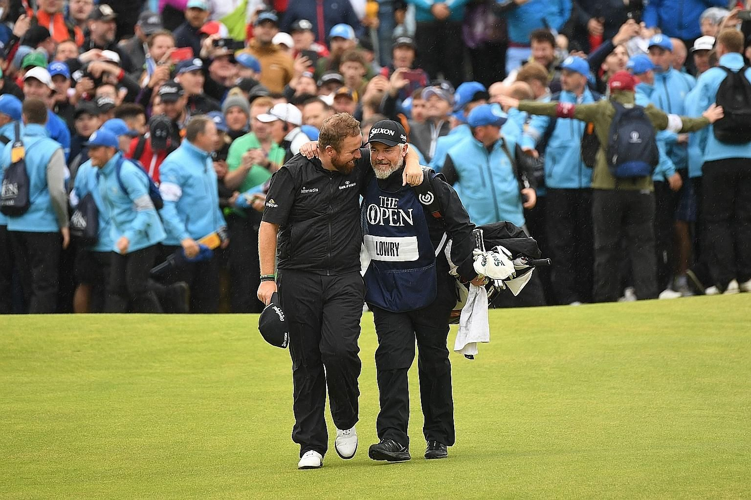 "Ireland's Shane Lowry puts his arm around his caddie Brian ""Bo"" Martin as they walked up the 18th fairway during the final round of the British Open last Sunday. PHOTO: AGENCE FRANCE-PRESSE"