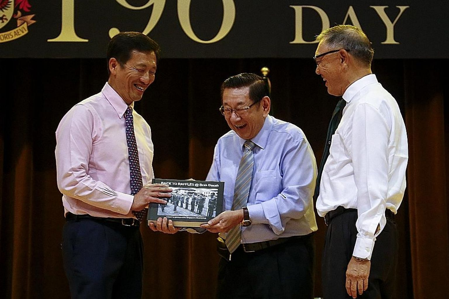 Education Minister Ong Ye Kung being presented the book Back To Raffles @ Bras Basah by Raffles Institution alumnus Er Kwong Wah. Beside them is RI board of governors chairman Choo Chiau Beng.