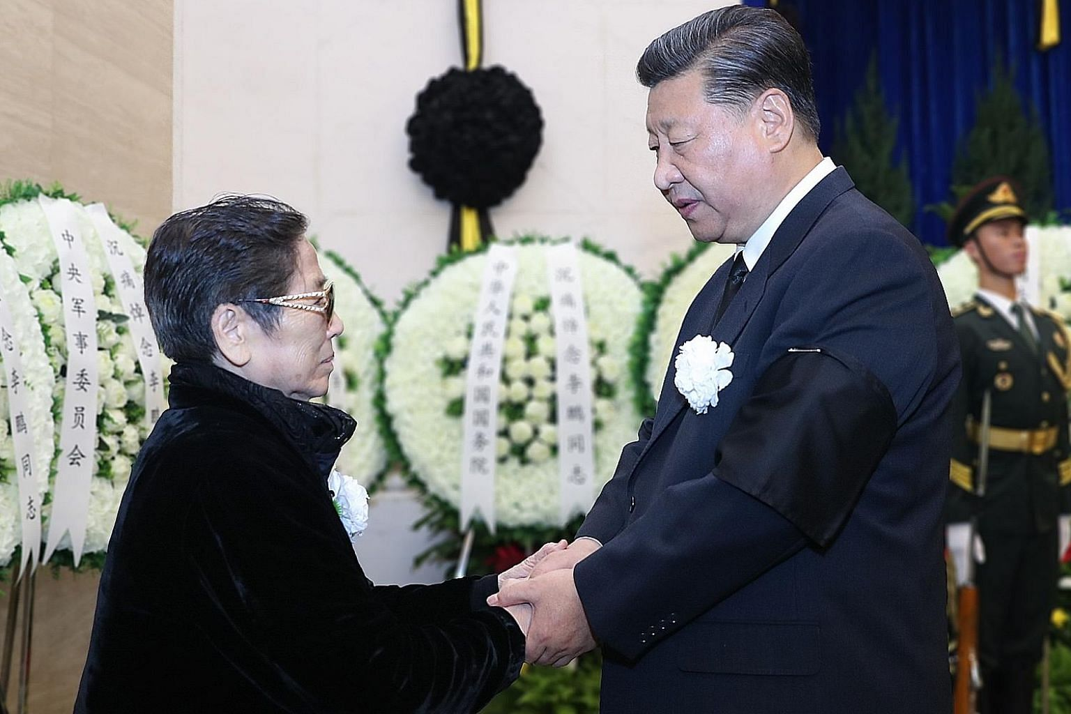 Far left: Then Premier Li Peng at a formal reception in Beijing in 1995. Left: Chinese President Xi Jinping expressing his condolences to Mr Li's family member in Beijing yesterday.