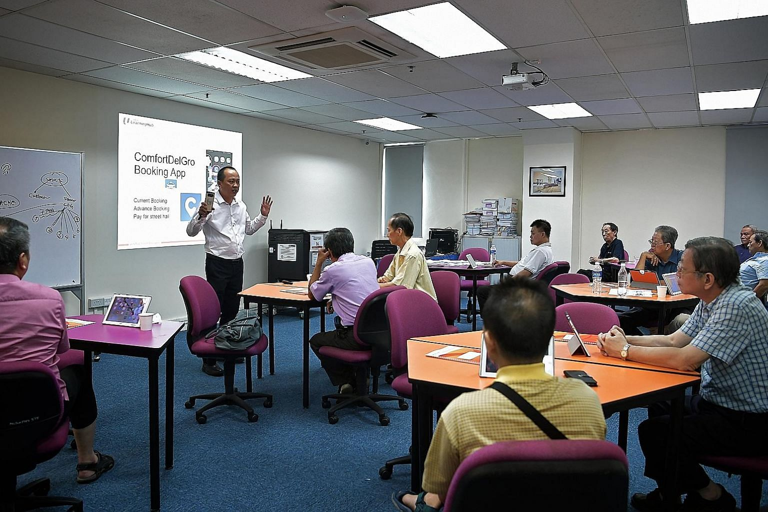 Cabbies attending a SkillsFuture for Digital Workplace class yesterday. The one-day programme is aimed at training 10,000 workers on how to better use technology in their jobs. Manpower Minister Josephine Teo, ComfortDelGro Taxi CEO Ang Wei Neng (thi
