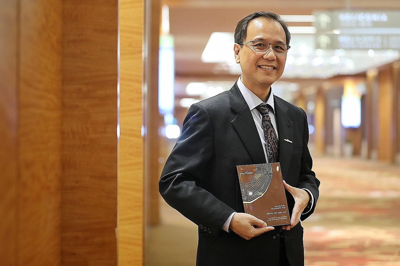 Mr Winston Sng, a senior human resource manager at the United Test and Assembly Centre, with his SkillsFuture Fellowships award at the SkillsFuture Fellowships and SkillsFuture Employer Awards ceremony at Marina Bay Sands yesterday.