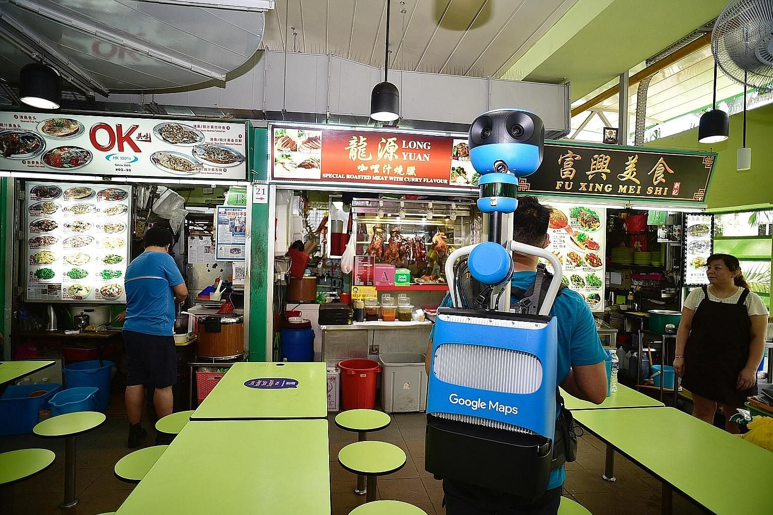 Street View Trekker operator Keith Lee, 24, capturing indoor imagery at Dunman Food Centre yesterday. All 114 hawker centres here will have their individual stalls marked with separate pins on the Google Maps app by early next year, showing their exa